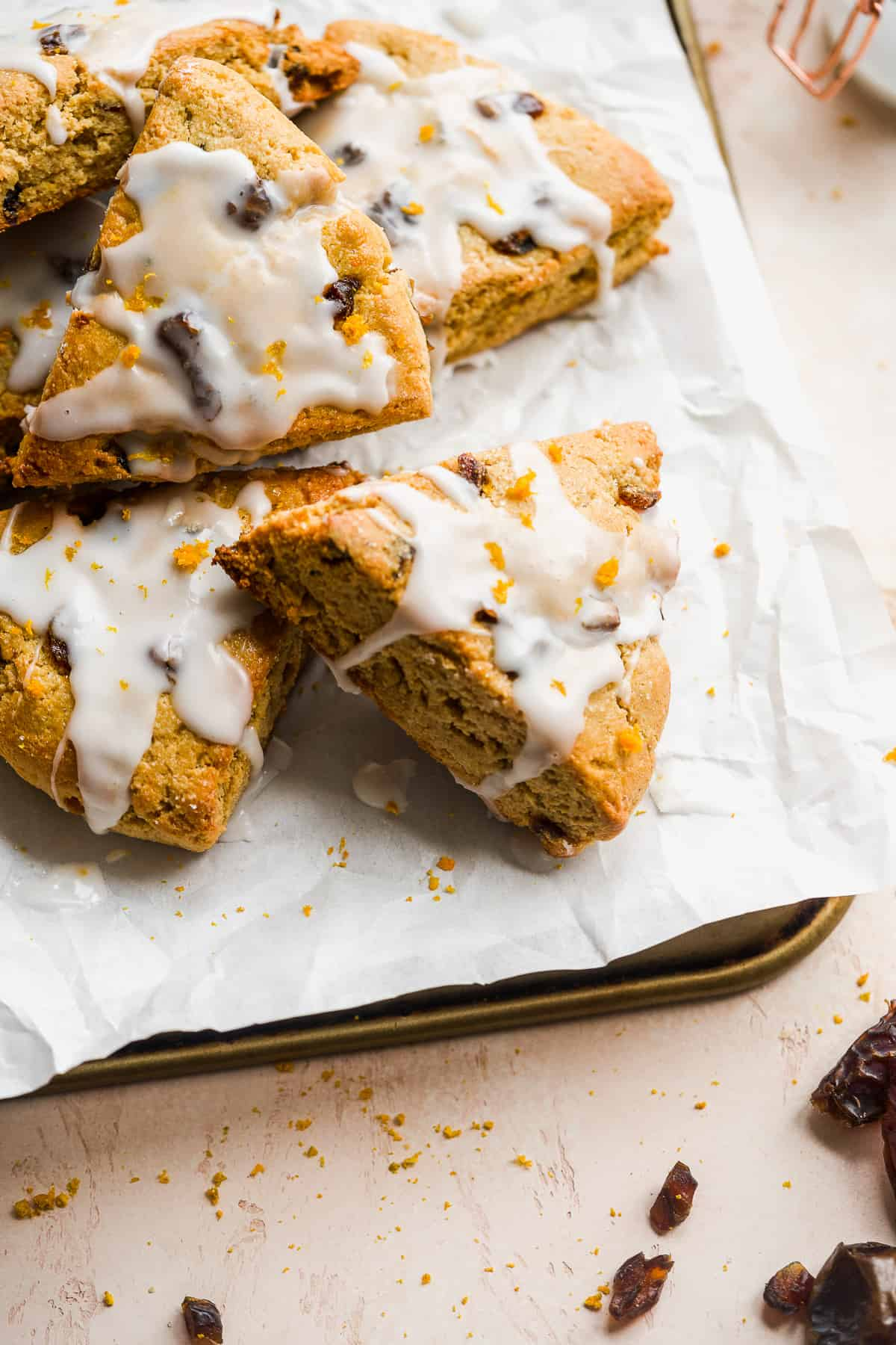 Triangular scones scattered in a pile on white parchment paper.