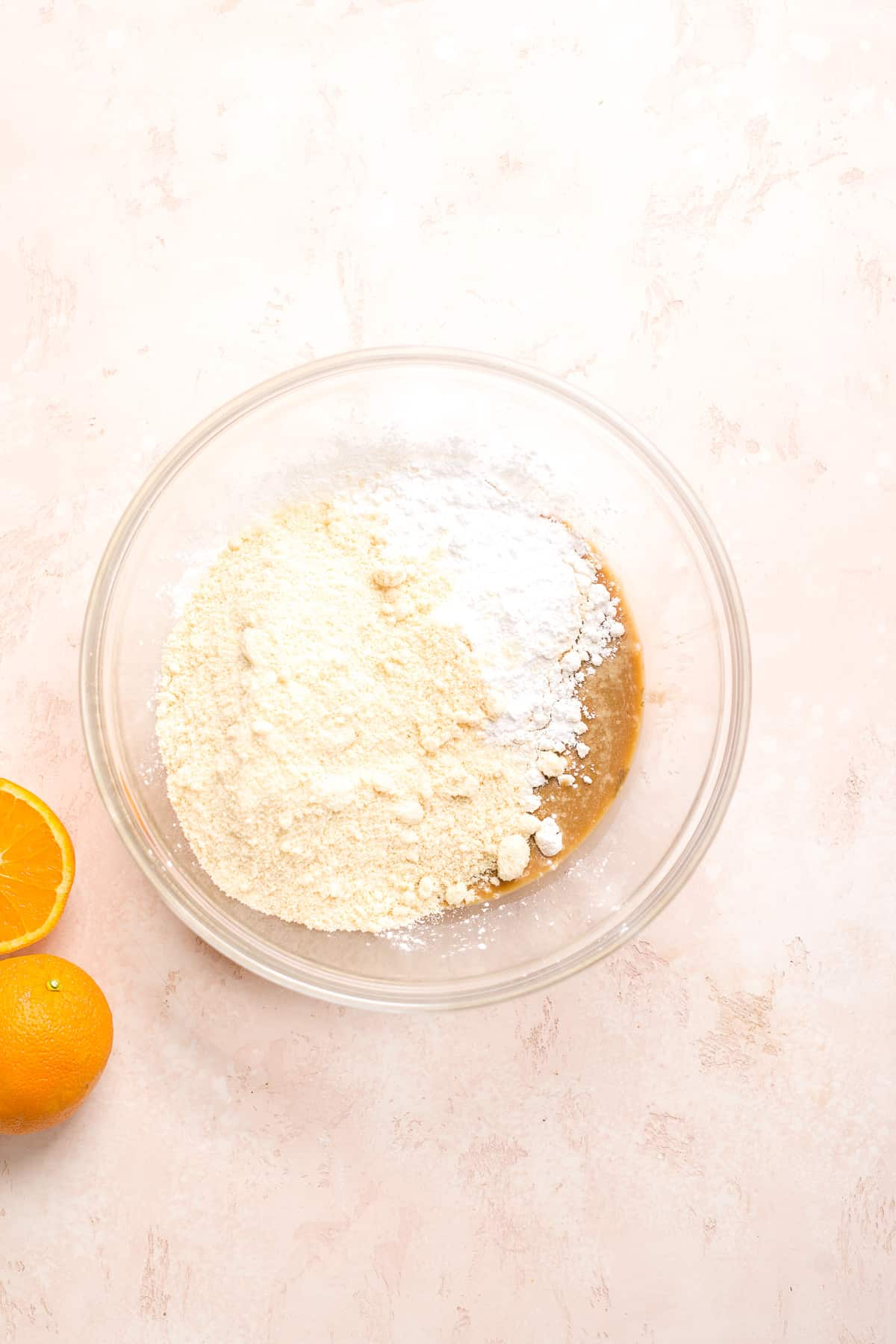 Large glass bowl with flour on top of tax mixture with orange off to the side.