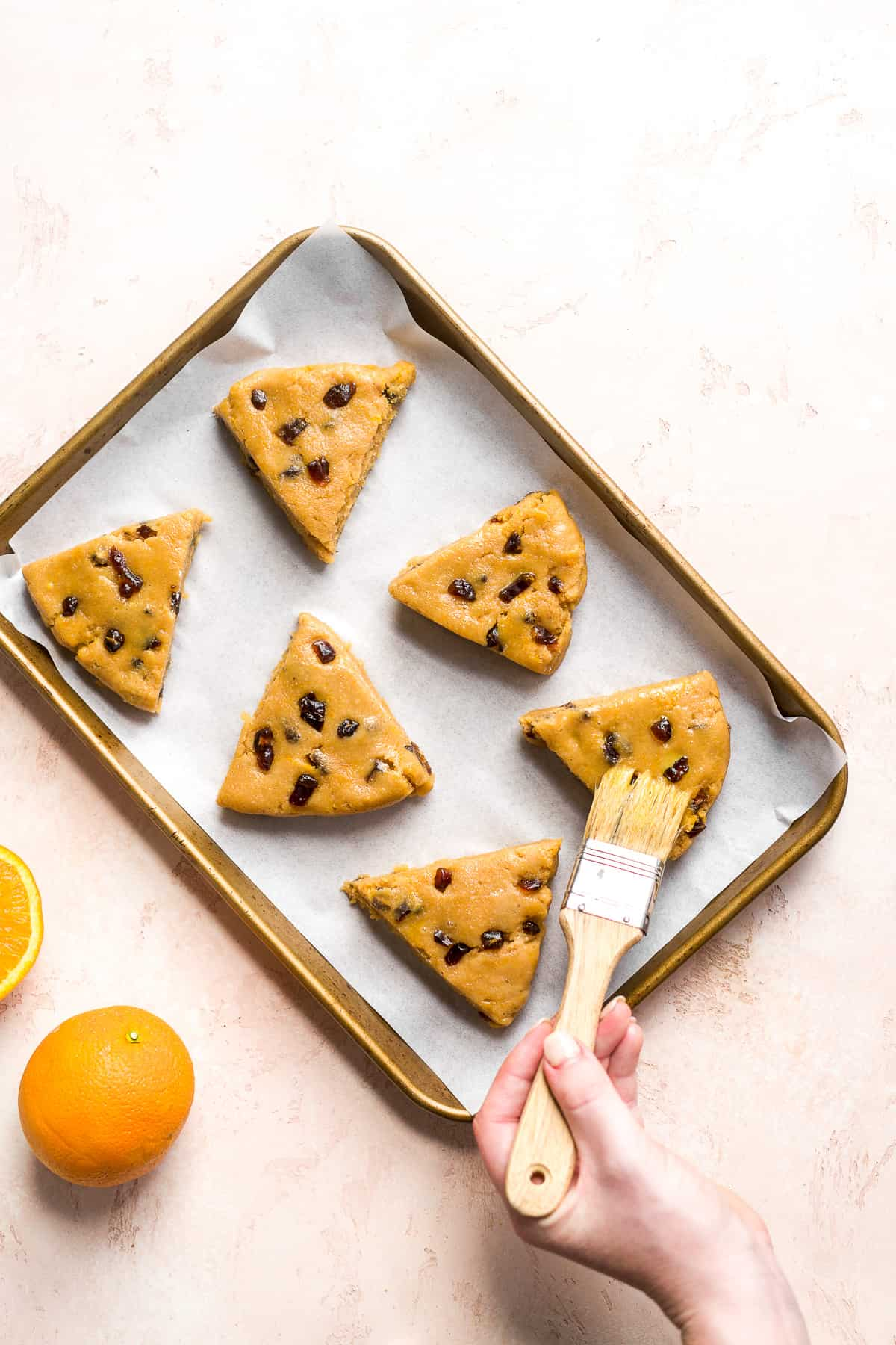 Triangular scones on a baking sheet with hand brushing the tops.
