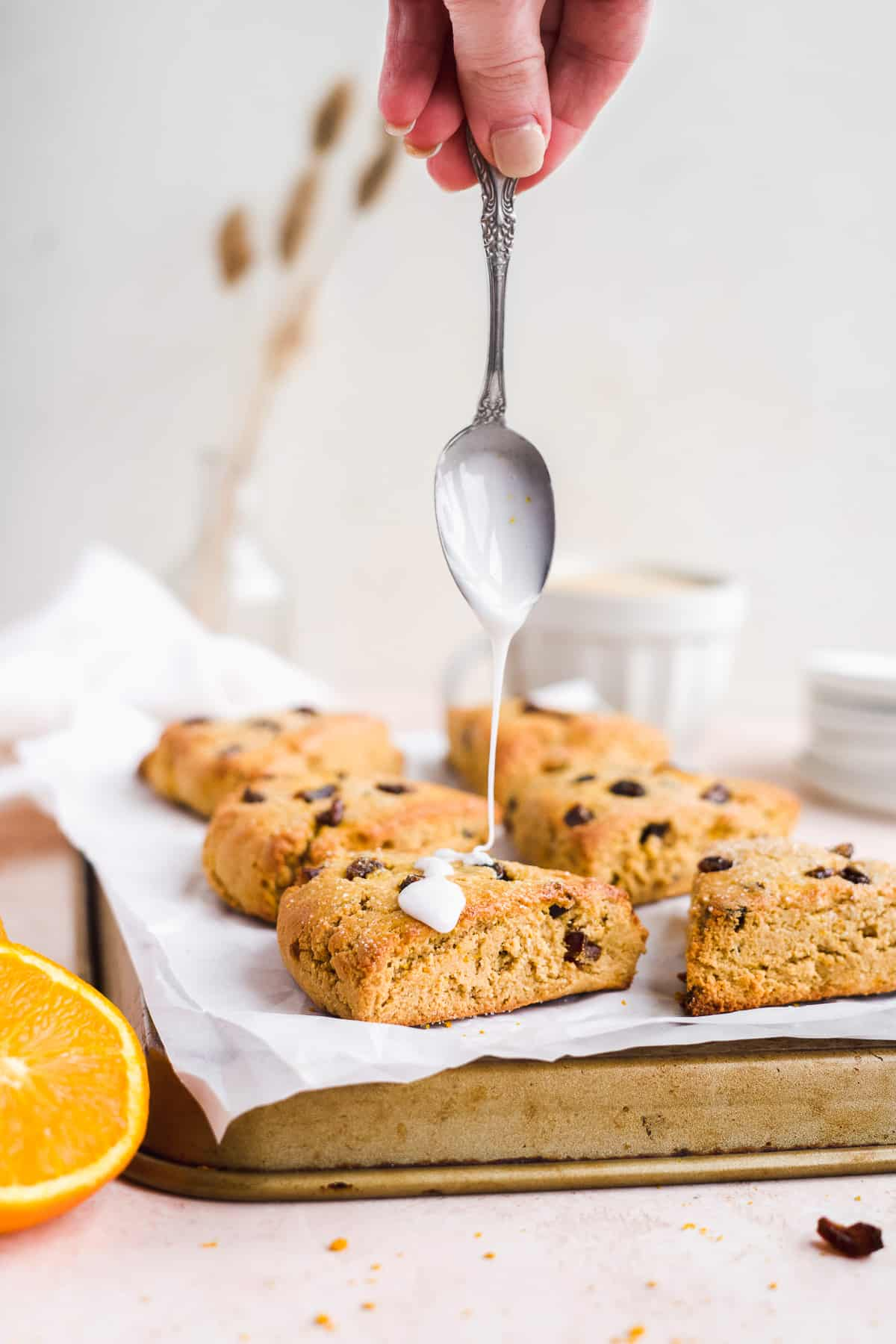 Hand drizzling white icing on top of baked scones on a baking sheet.
