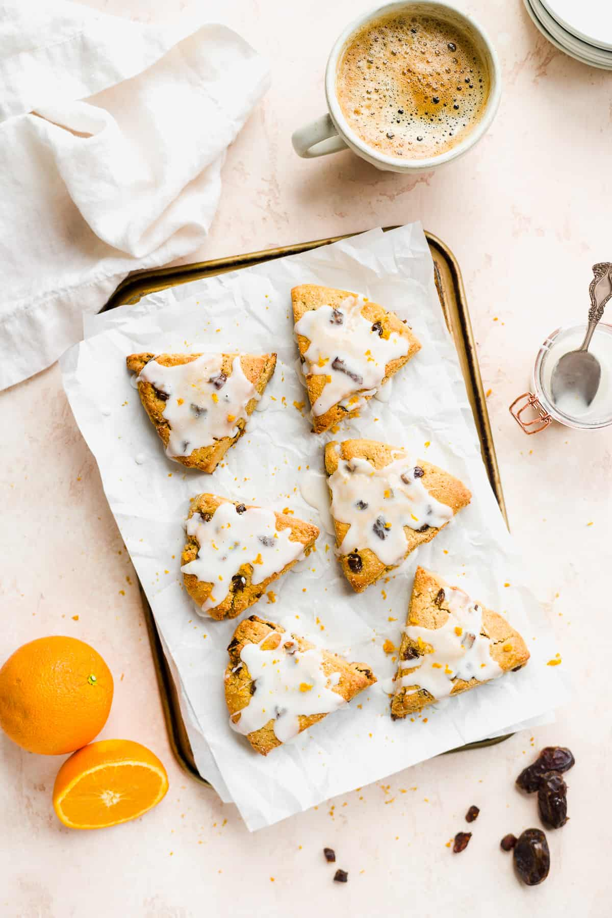 Golden scones on white paper on top of a baking sheet with orange and dates on the surface.