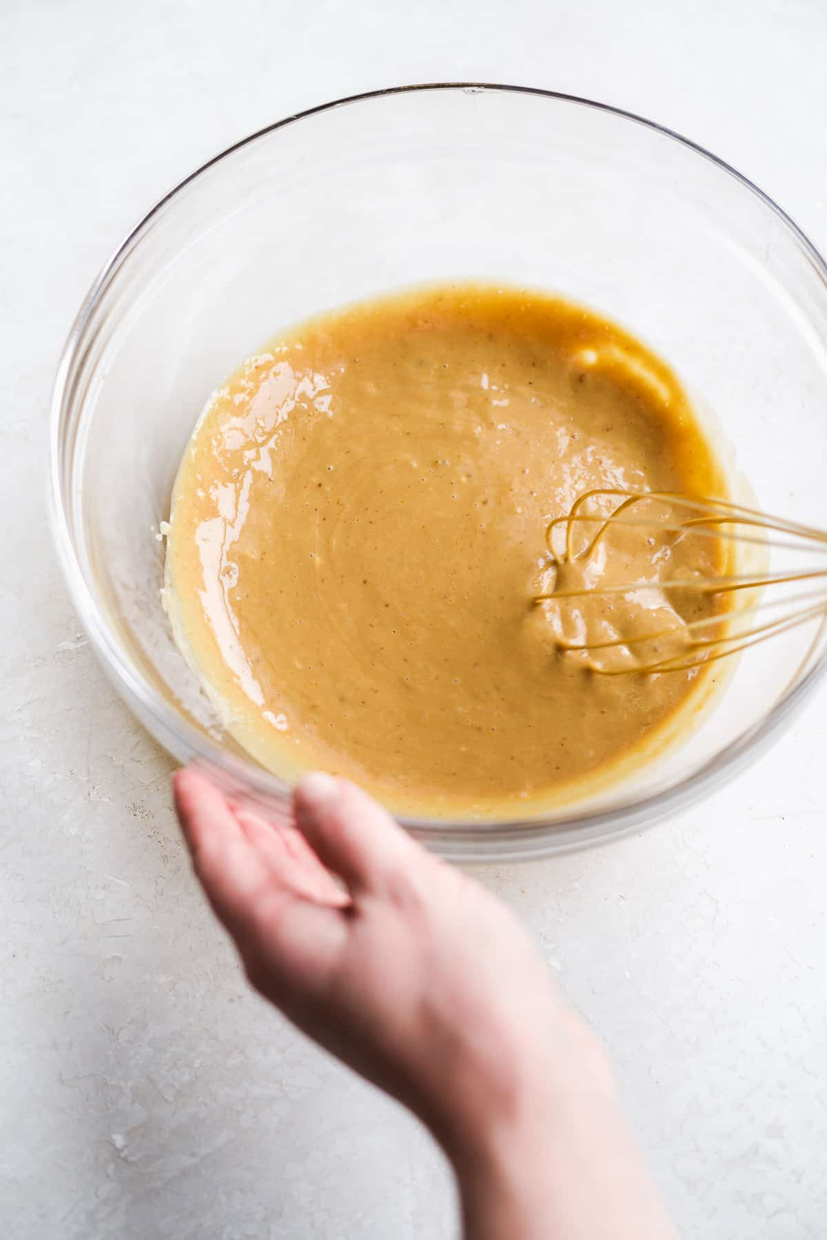Glass bowl with hand whisking peanut butter colored mixture on white surface.