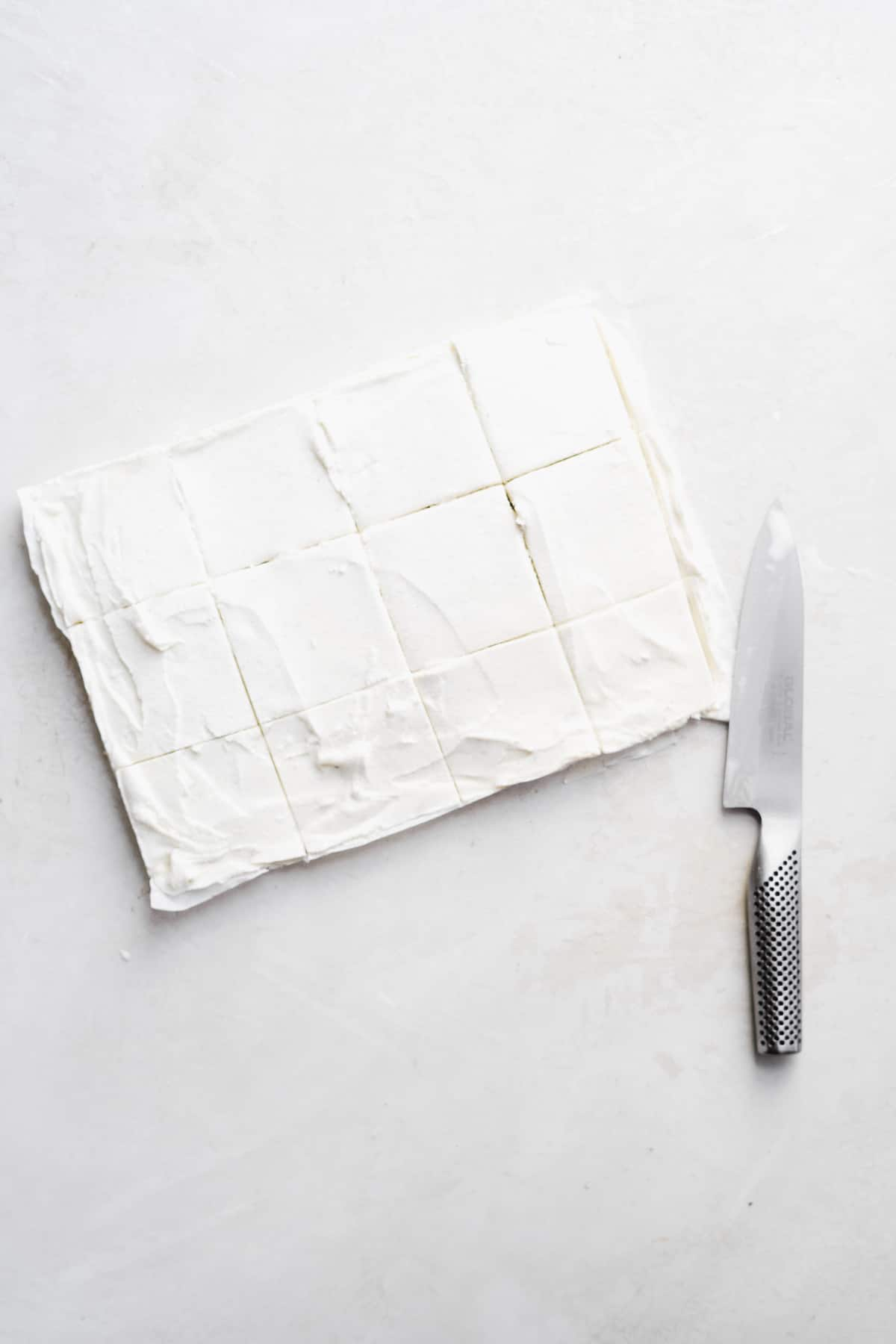 Rectangular piece of ice cream on a white surface sliced into squares with a knife.