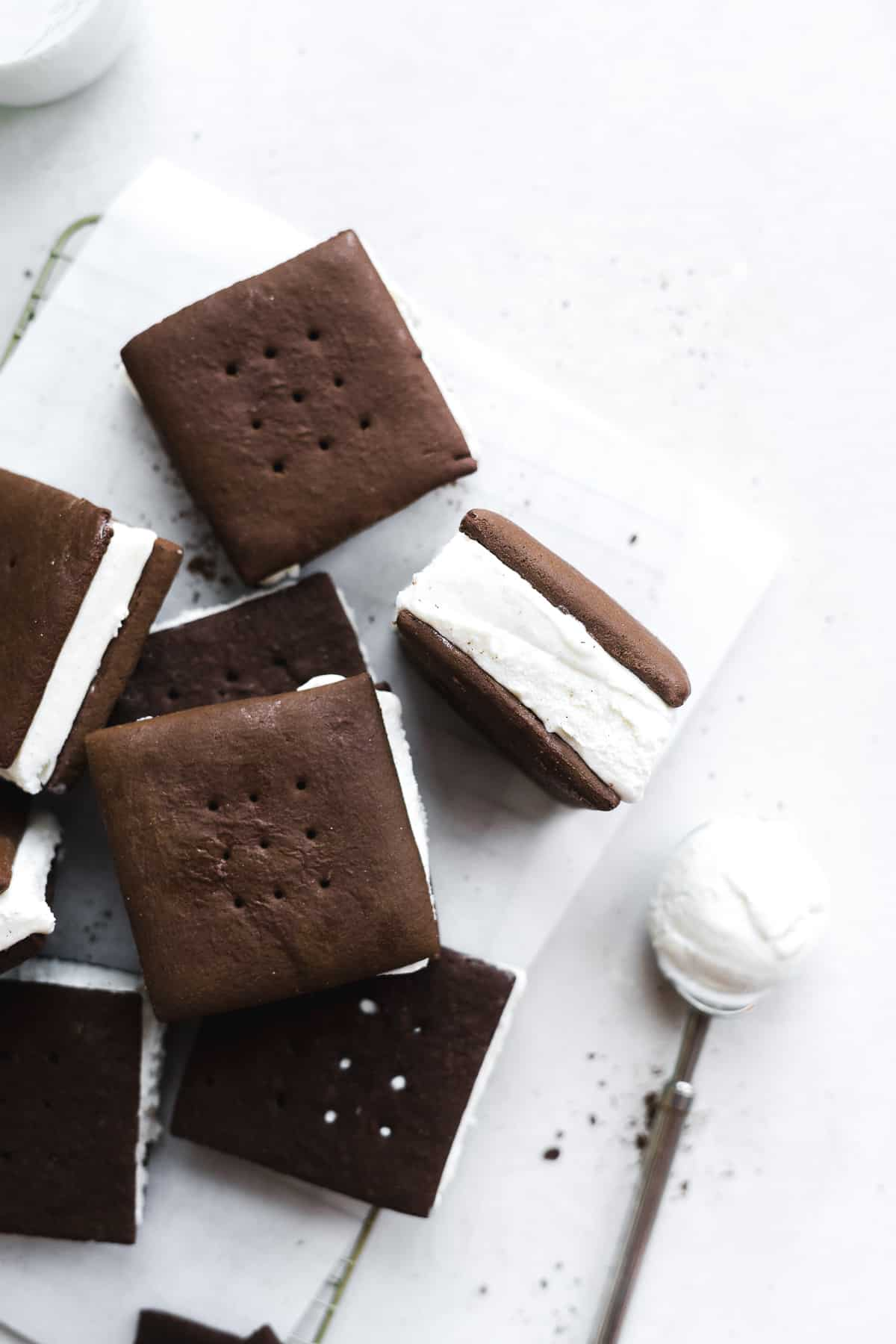 Chocolate ice cream sandwiches scattered on surface with one tipped upwards and an ice cream scoop on the side.
