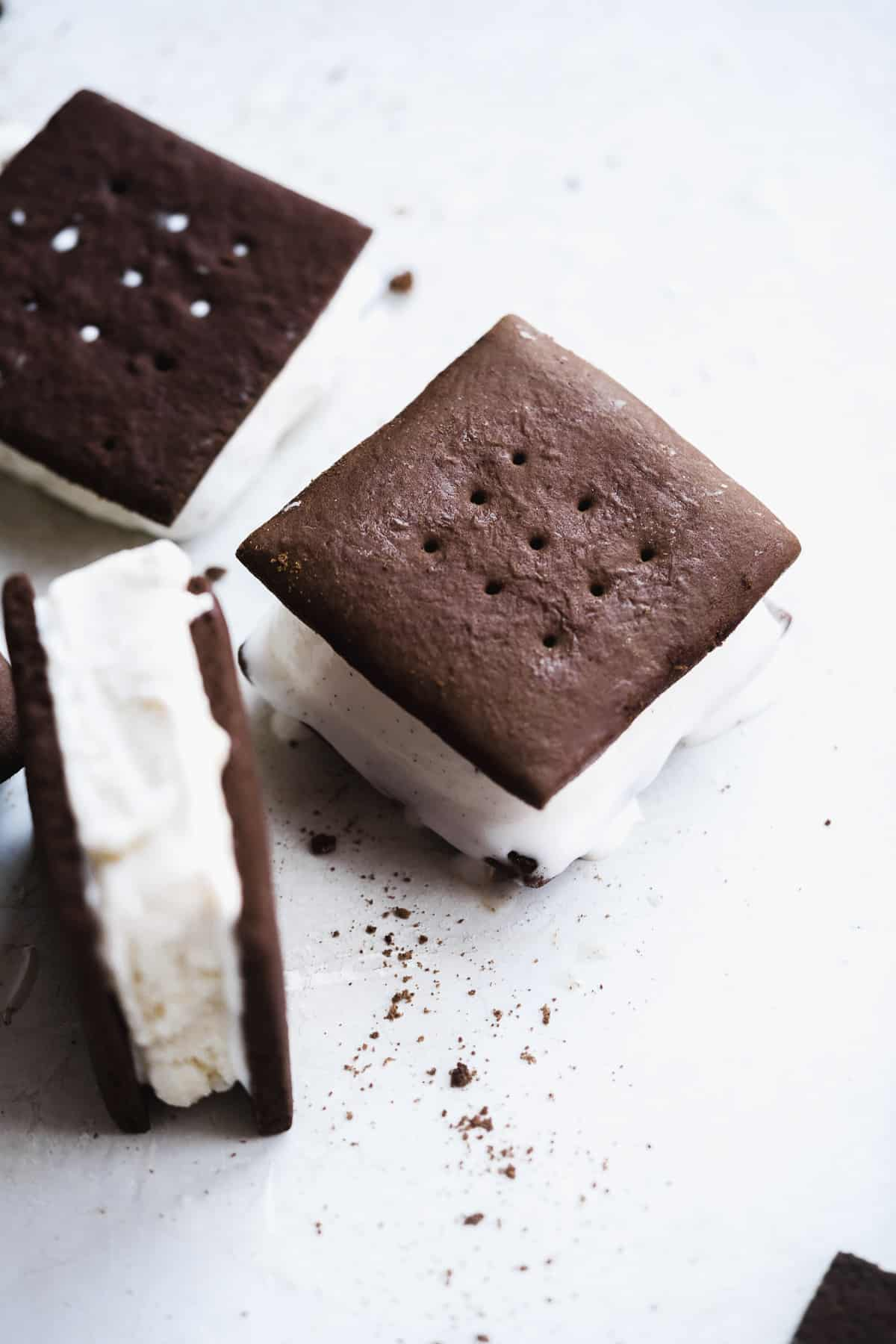 Chocolate ice cream sandwich with ice cream melting off the sides and one flipped upwards.