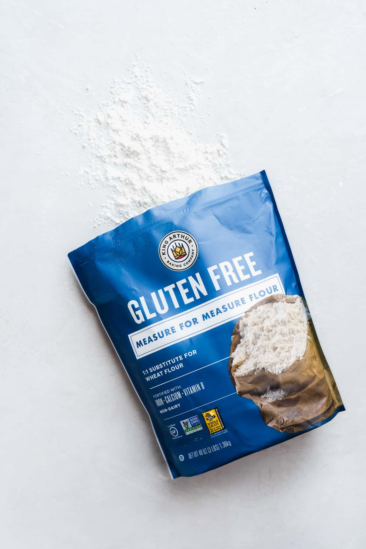 Image of blue bag of flour laying on a white surface with some flour spilling out the top.