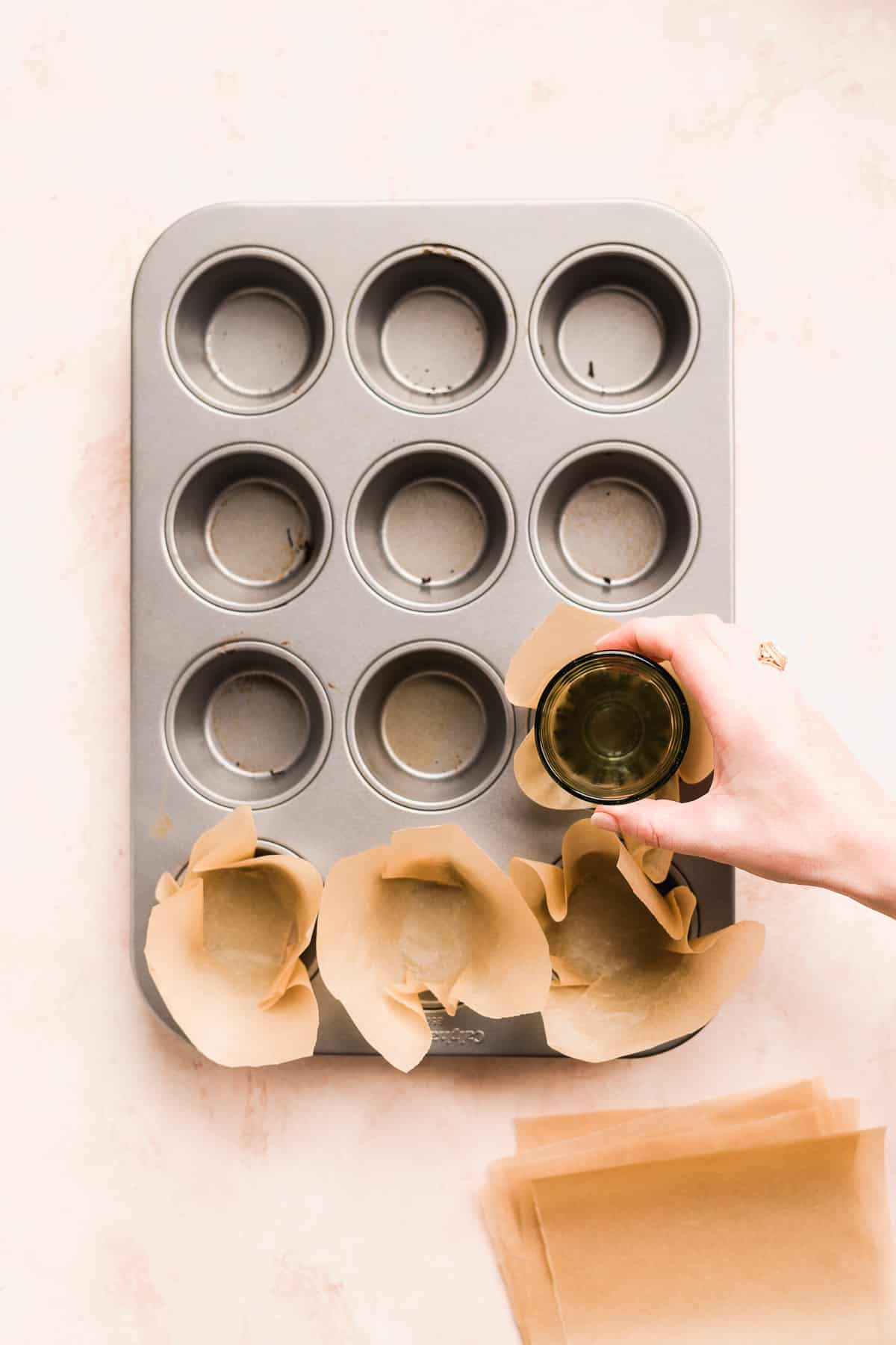 Hand placing brown parchment paper into a muffin tin to create liners.