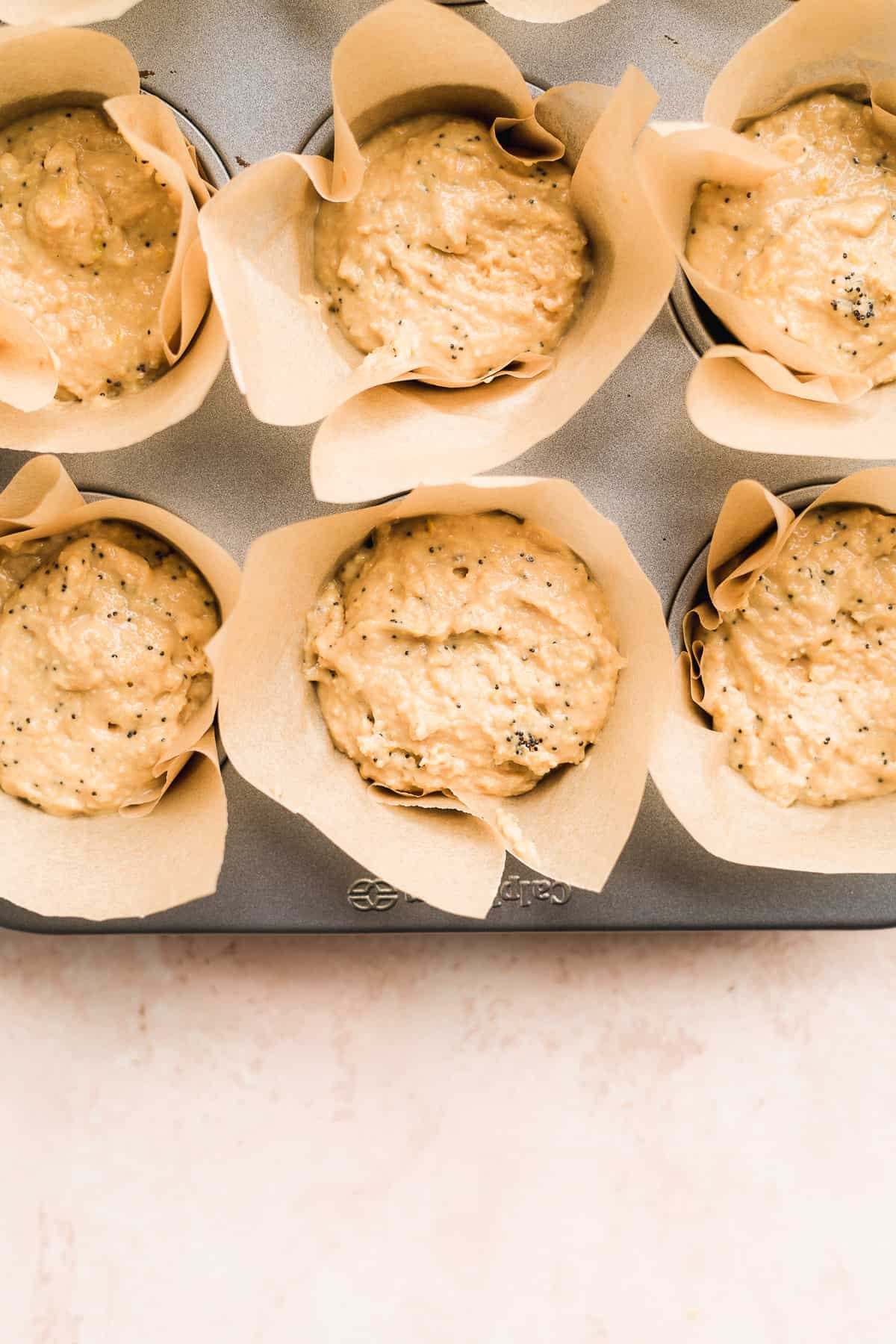 Muffin tin filled with batter in brown liners.