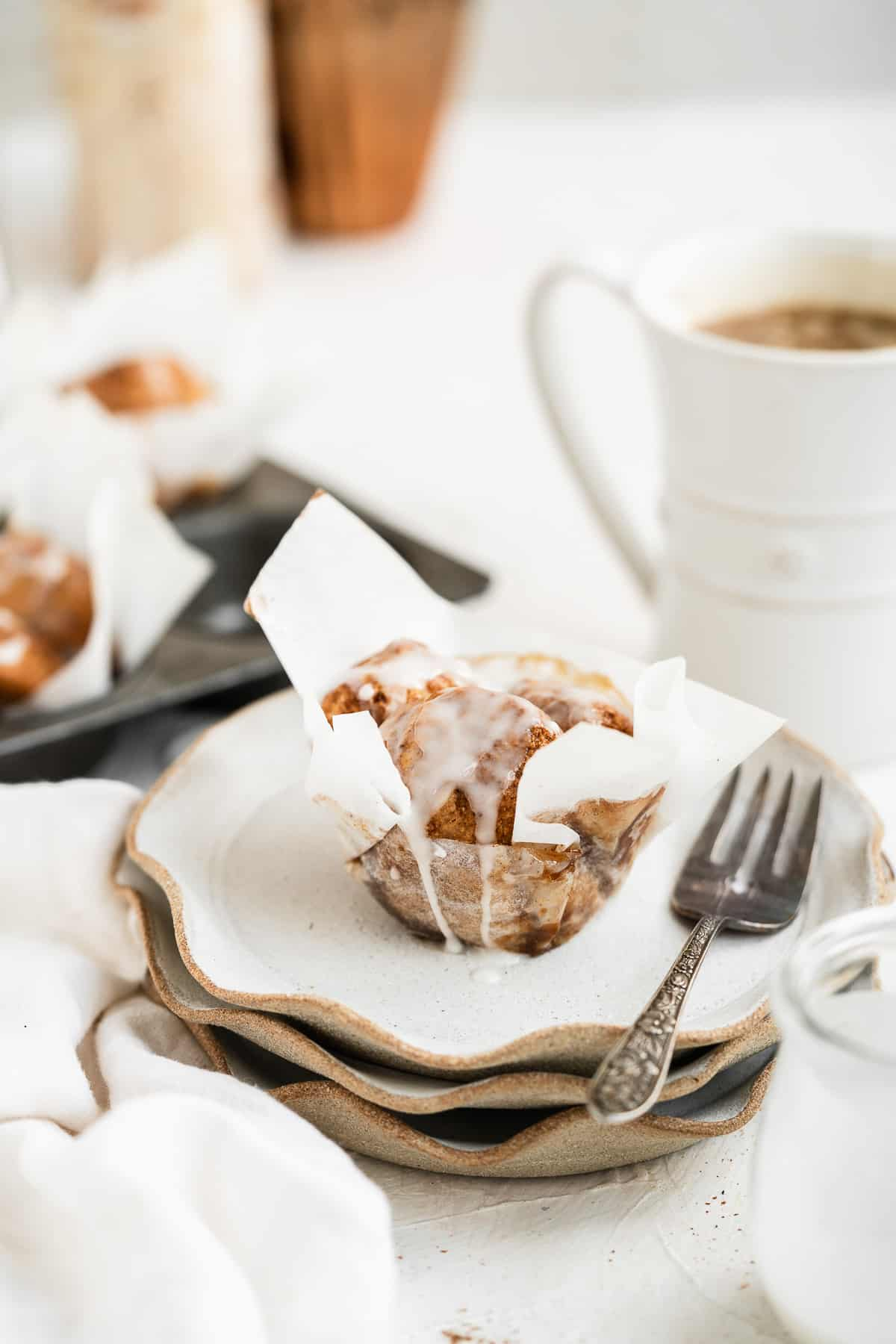 Single muffin sitting on top of a stack of plates with a fork to the side and coffee in the background.