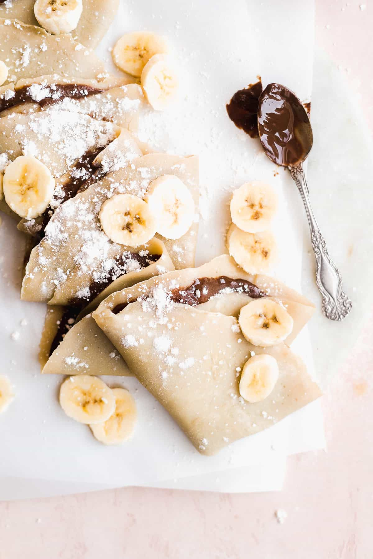 Chocolate crepes in a line on parchment paper.