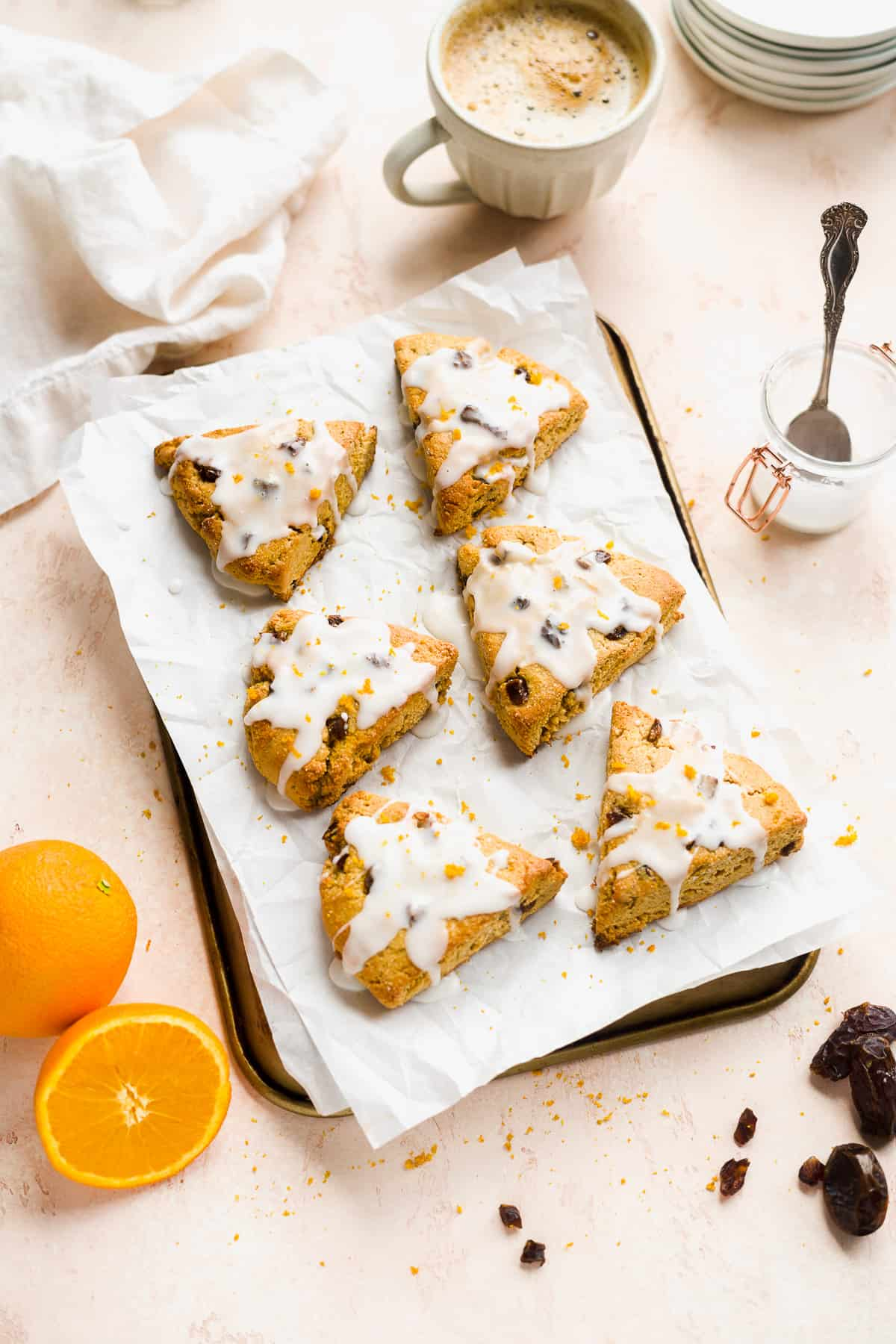 Triangular scones with glaze on parchment paper on top of a baking sheet with orange on the side.