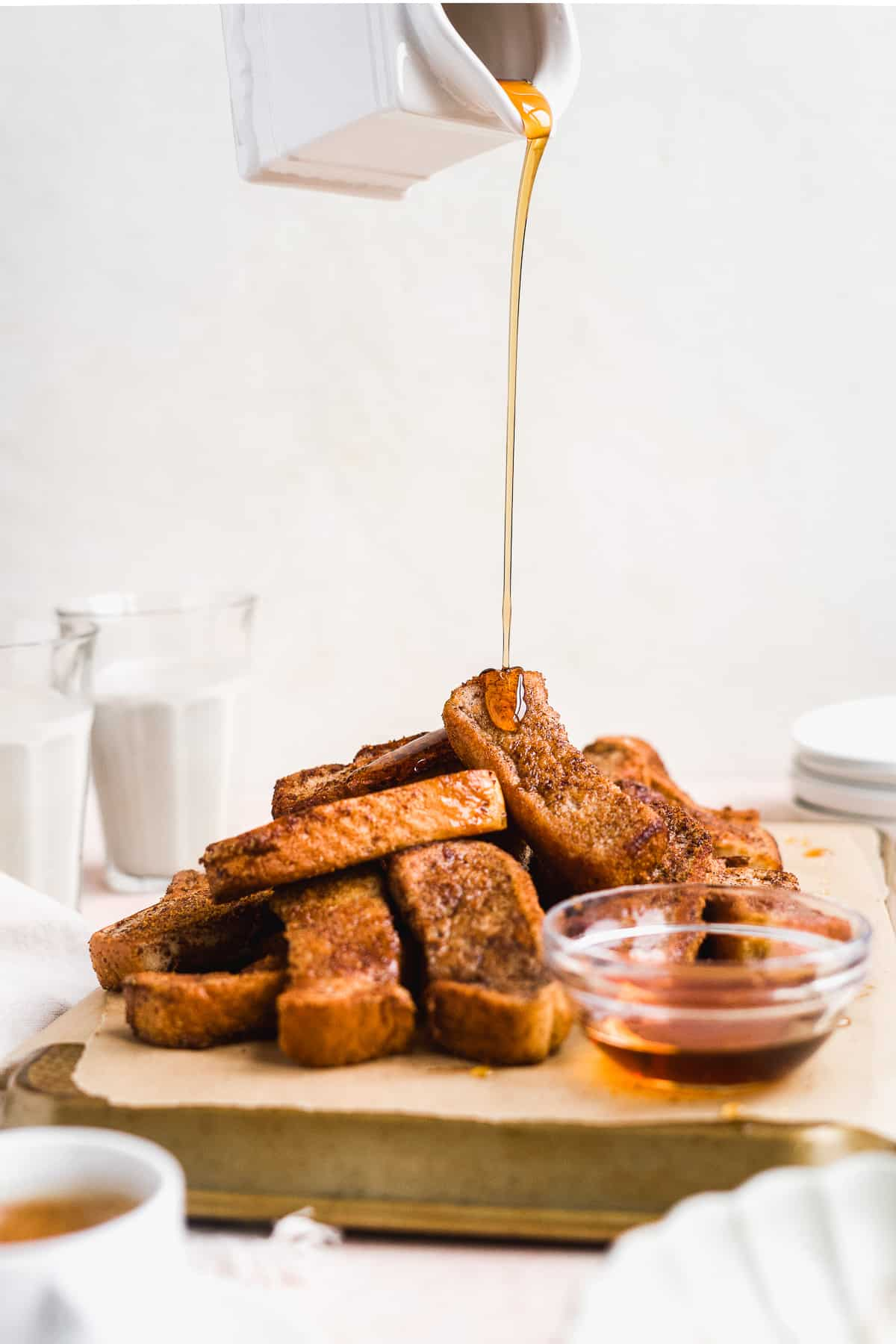 Maple syrup being poured on top of a pile of french toast sticks.