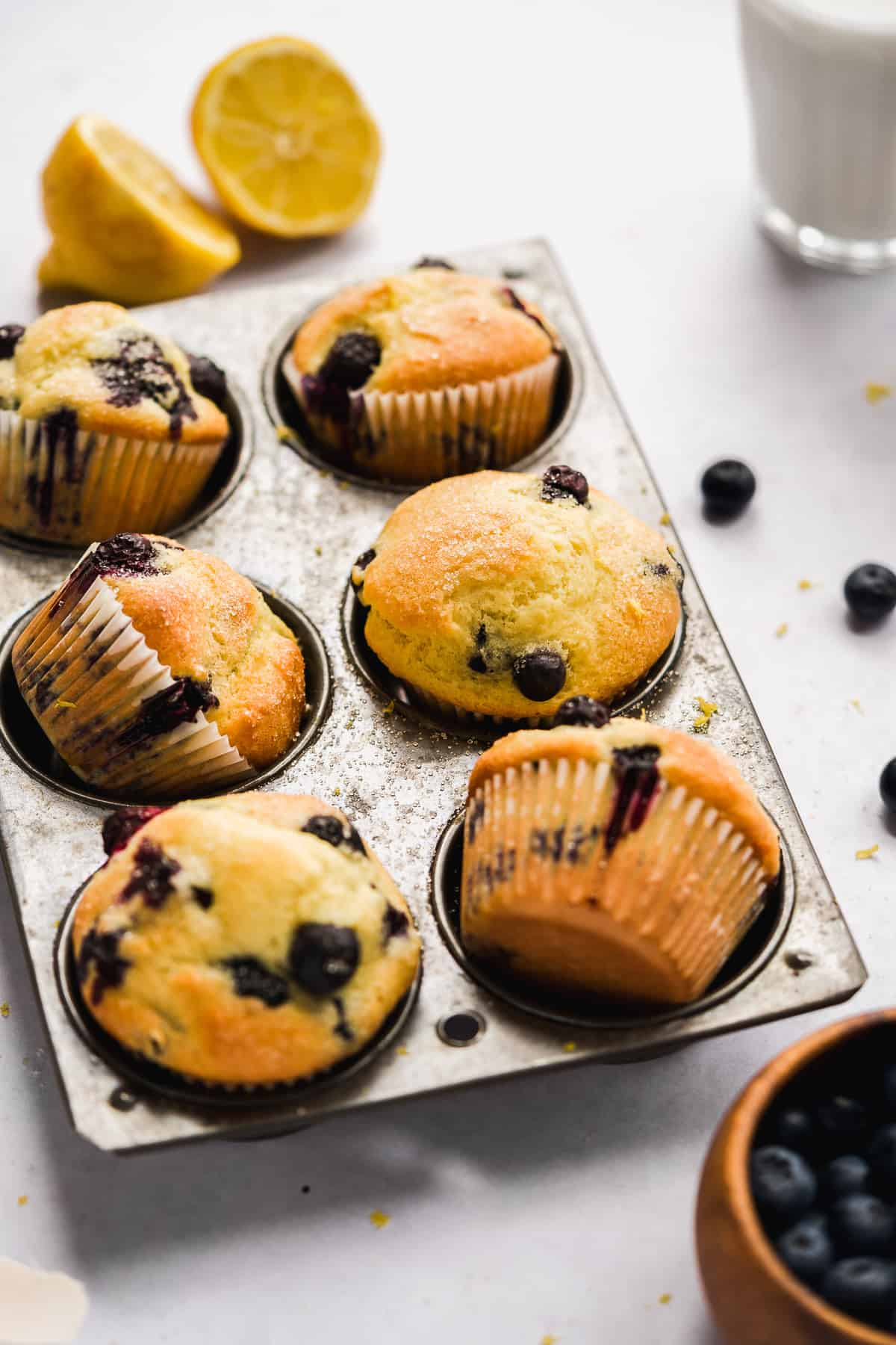 Blueberry muffins in a muffin tin with a few tipped sideways and blueberries on the surface.