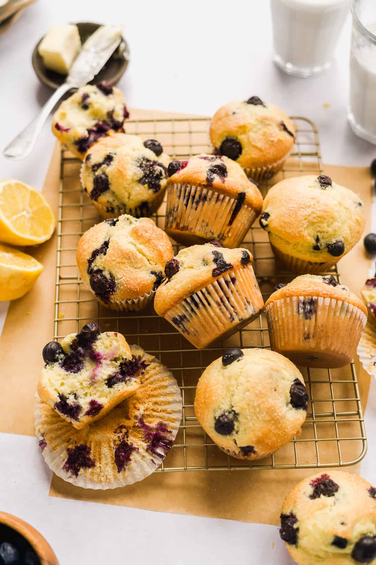 Blueberry muffins scattered on a wire cooling rack with parchment paper beneath.