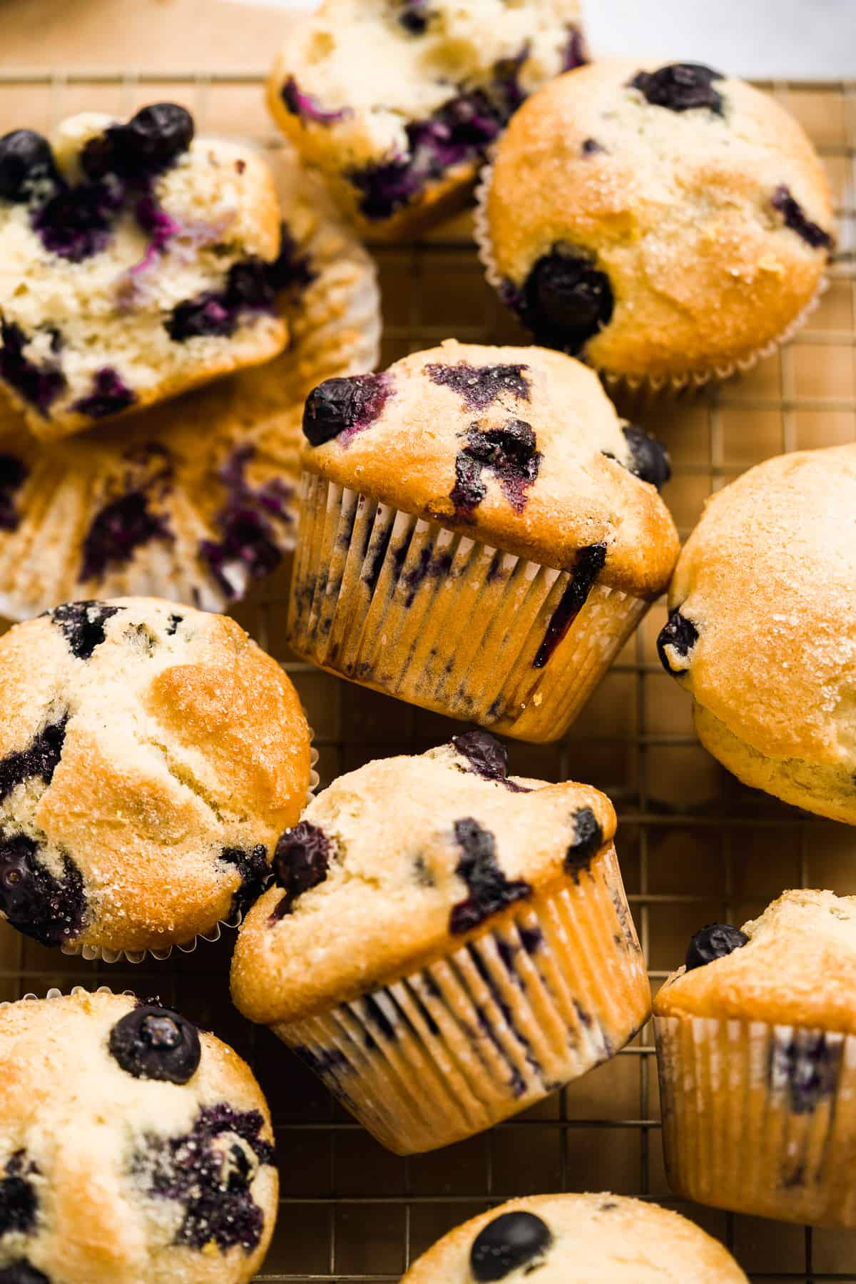 Blueberry muffins scattered on wire cooling rack.