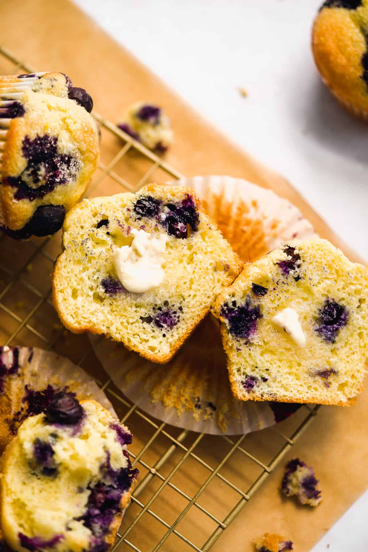 Blueberry muffin sliced in half on a wire rack with butter.