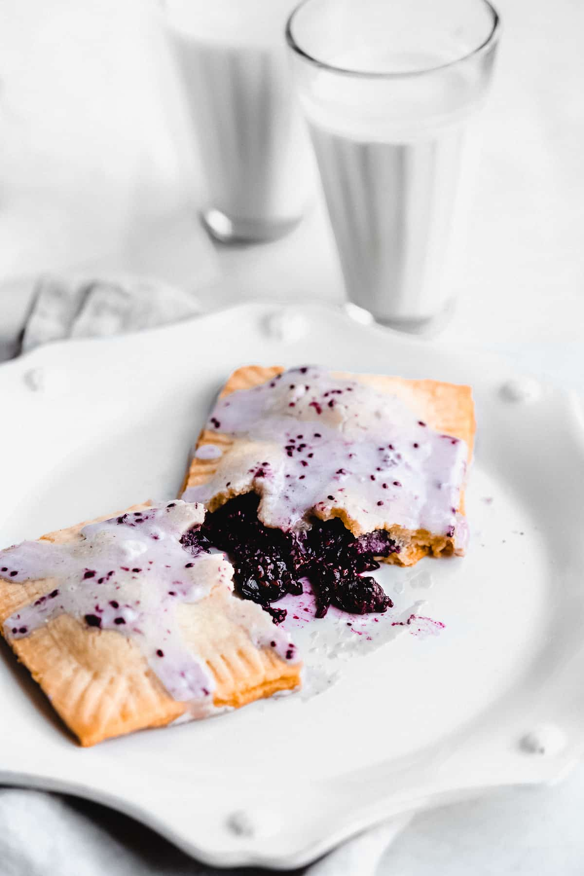 Pop tart broken open on a plate with blueberry jam spilling out and frosting.