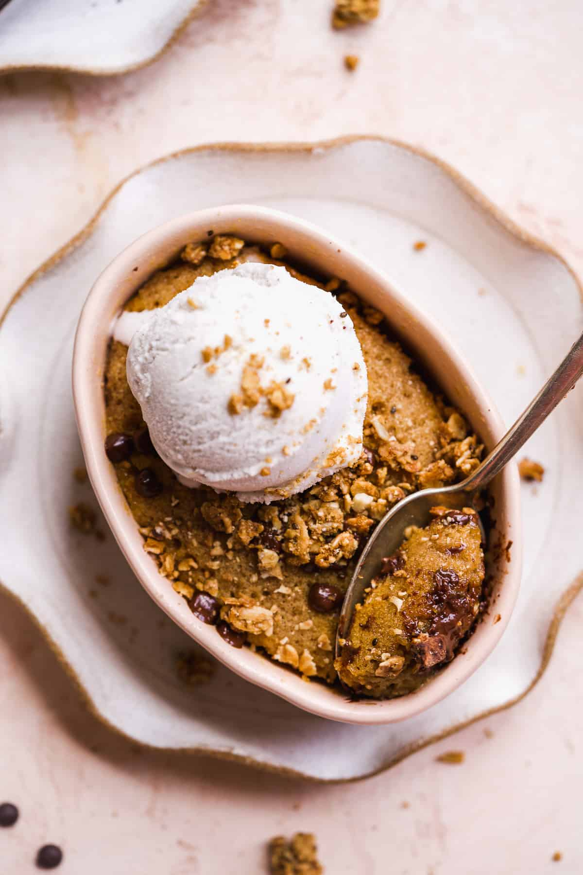 Oval dish with chocolate chip cookie baked inside and ice cream scoop on top.
