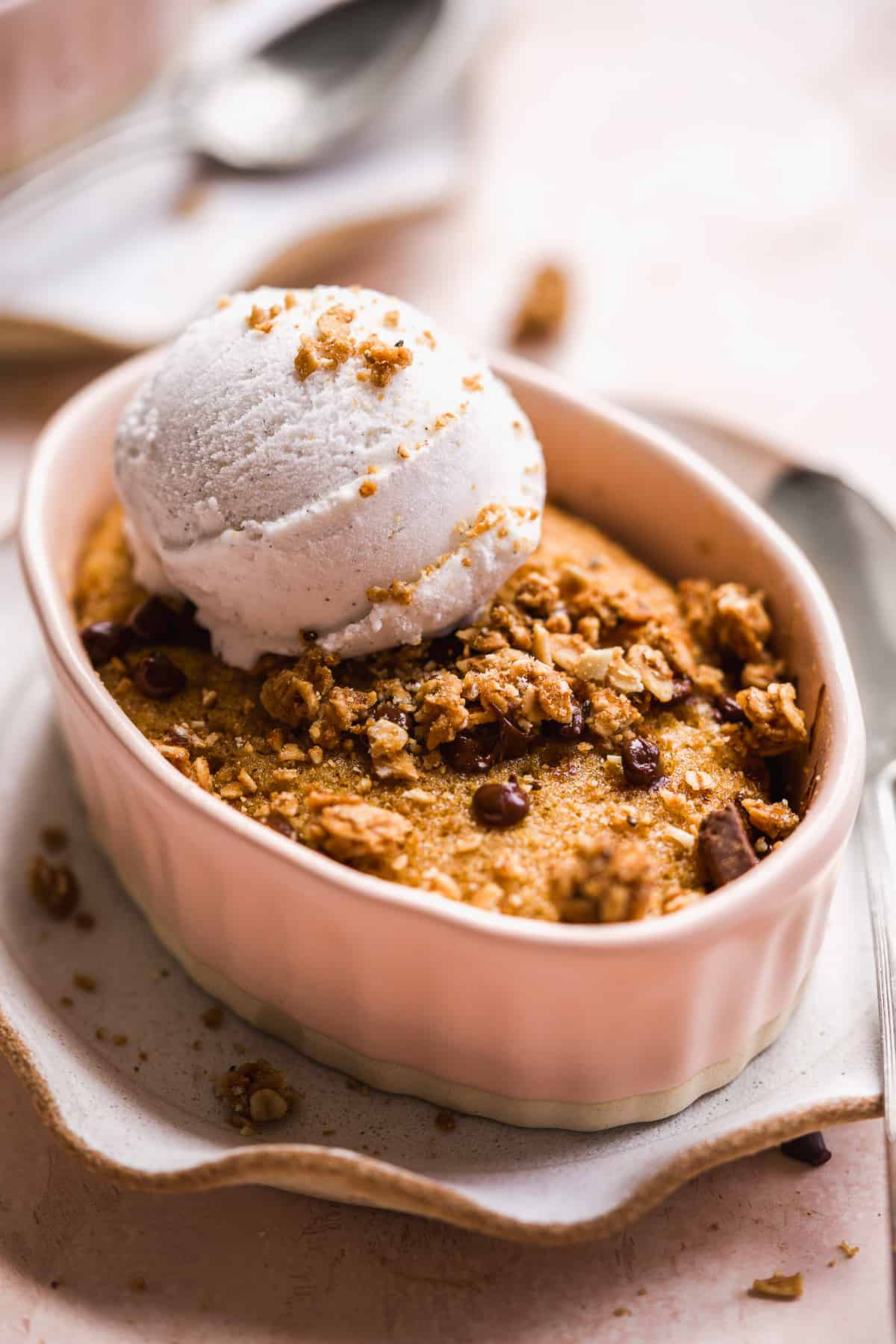Oval ramekin with a chocolate chip cake baked inside and ice cream scoop on top.