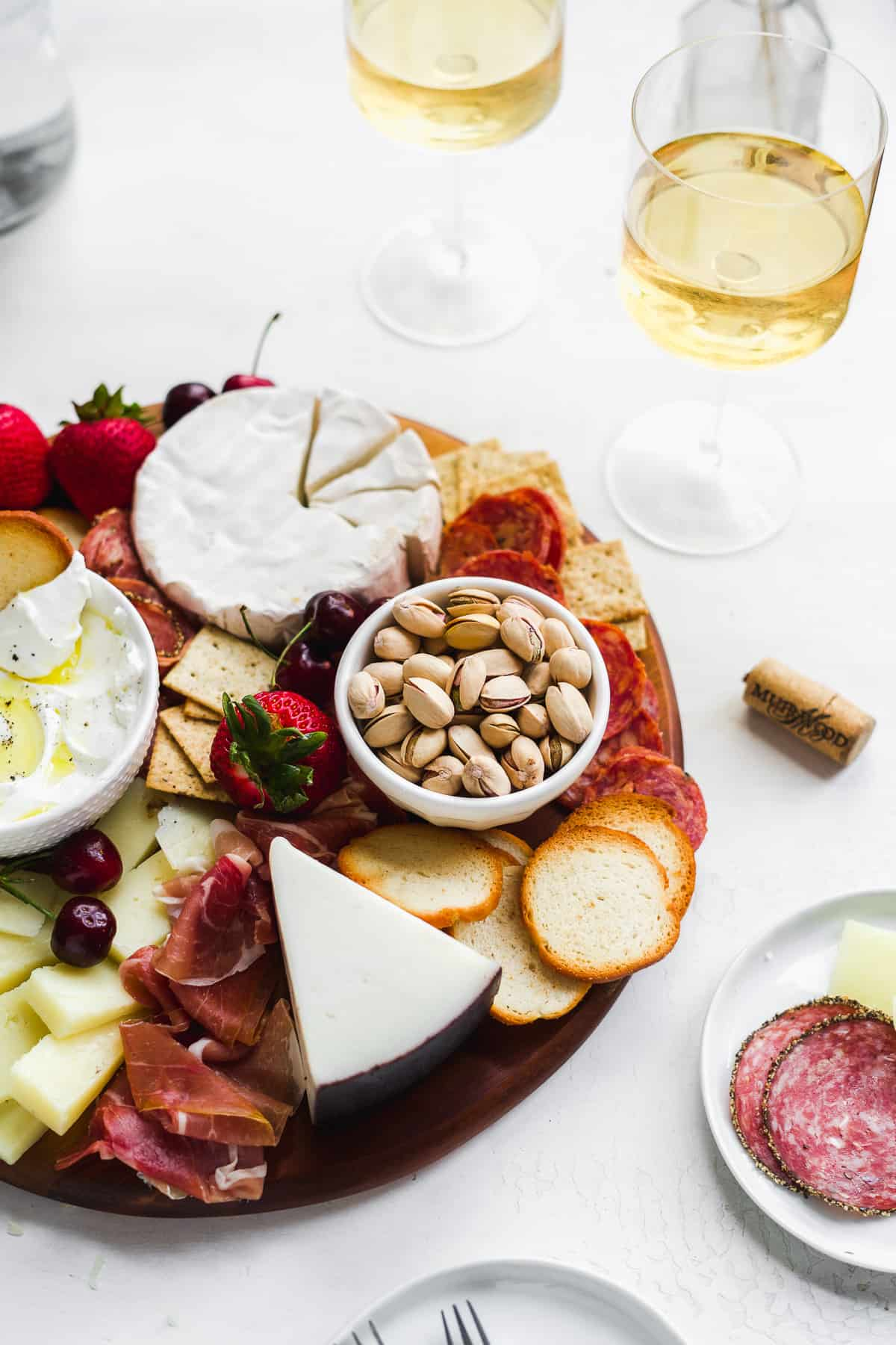 Charcuterie board with nuts and fruit and wine glasses in the background.