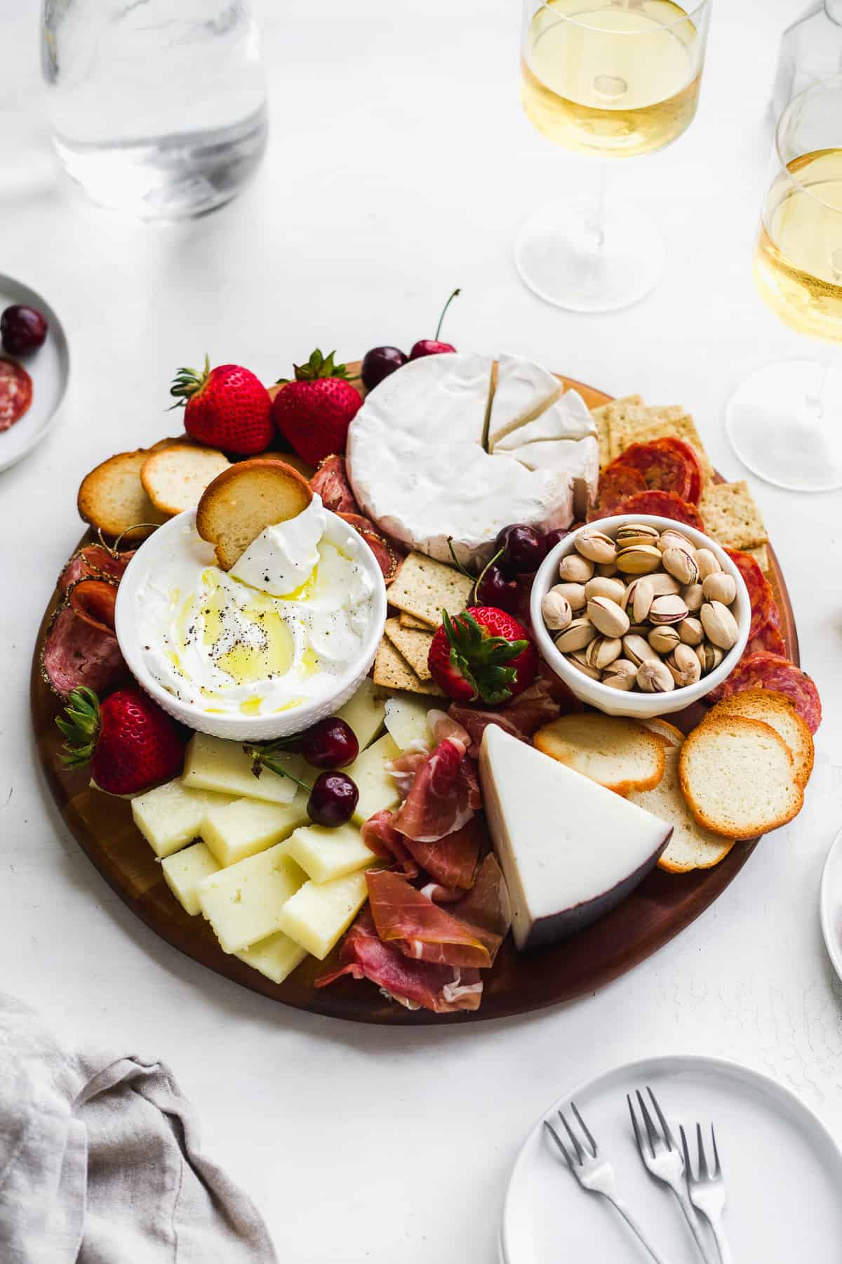 Wooden board filled with meats and cheeses and wine on the side.