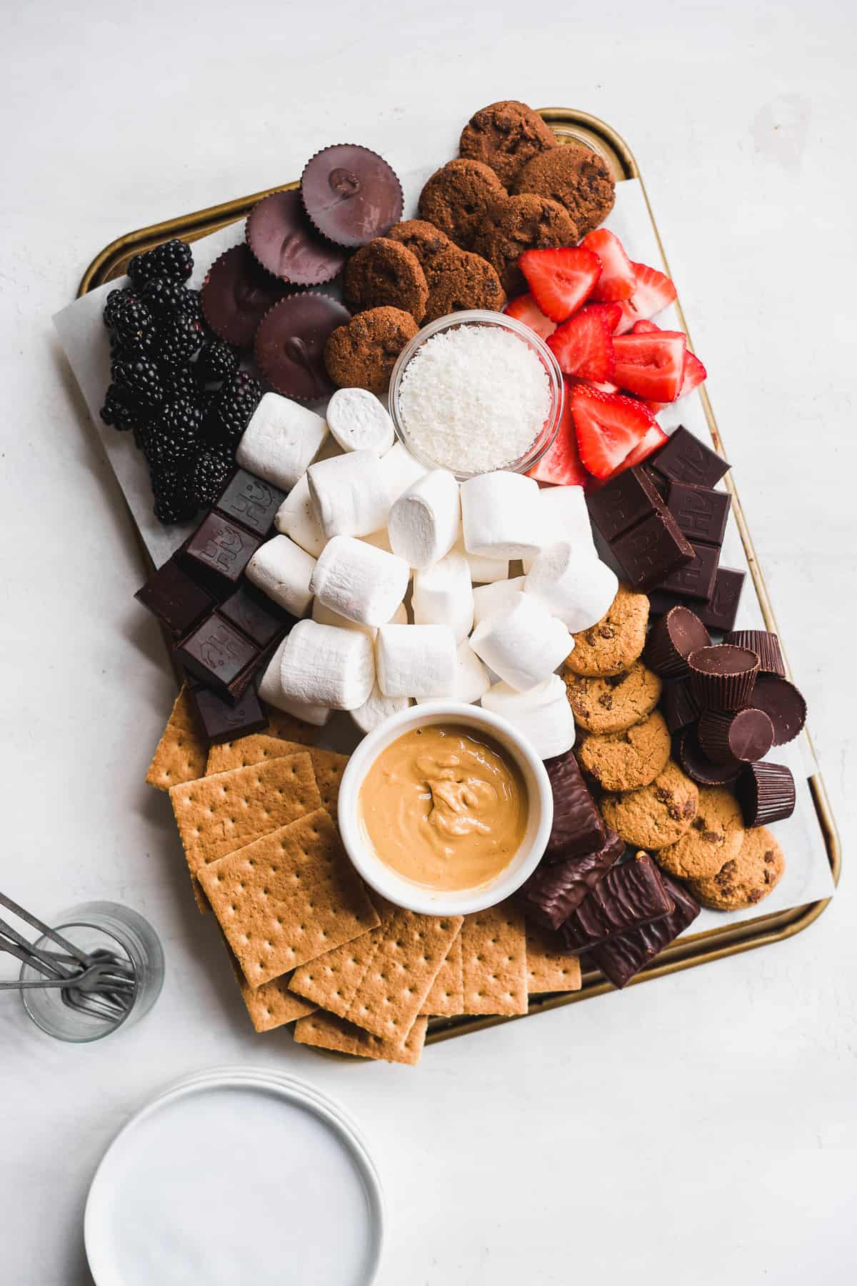 Overhead view of a platter with dessert toppings spread out on a white surface.