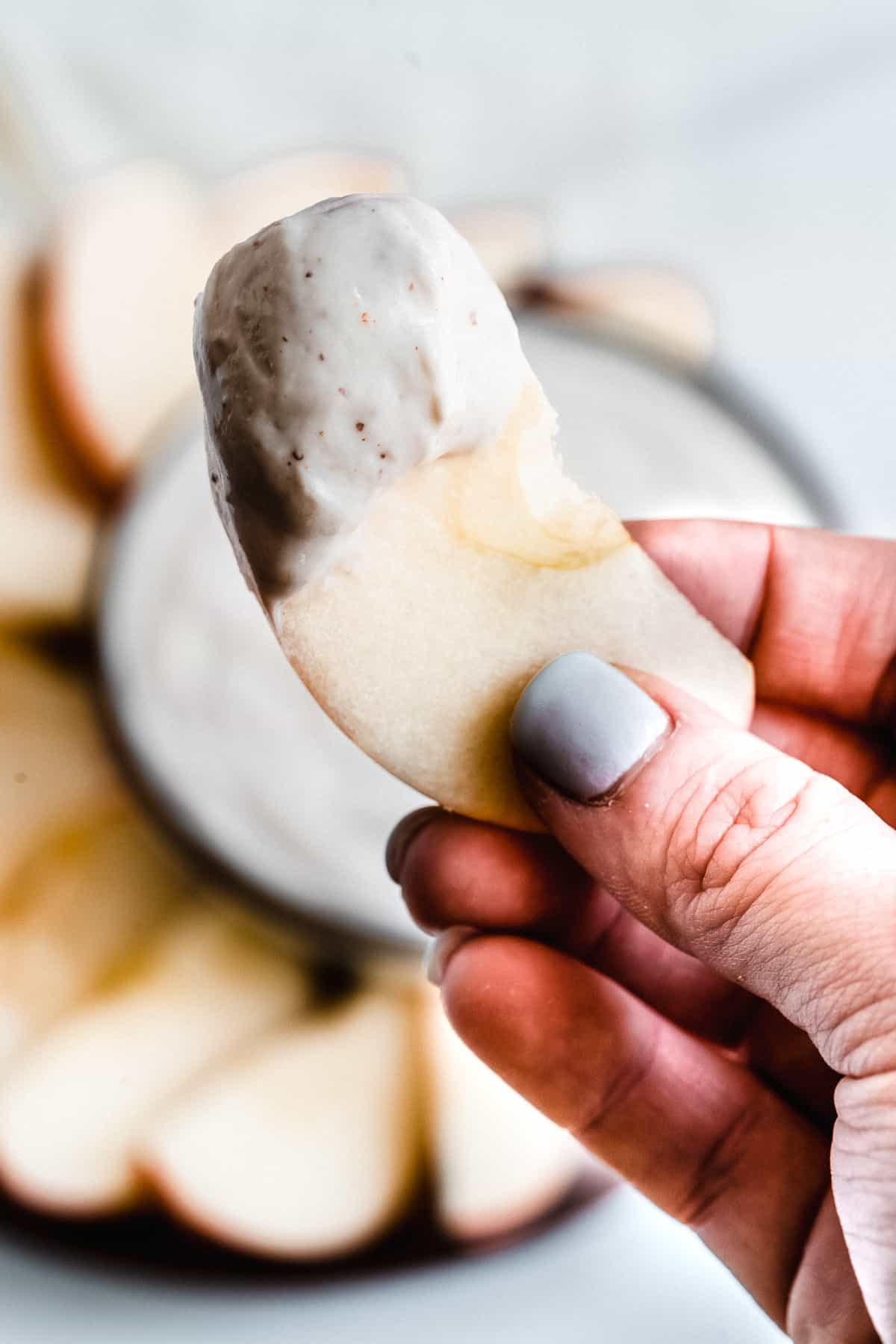 Hand holding apple slice with greek yogurt dip.