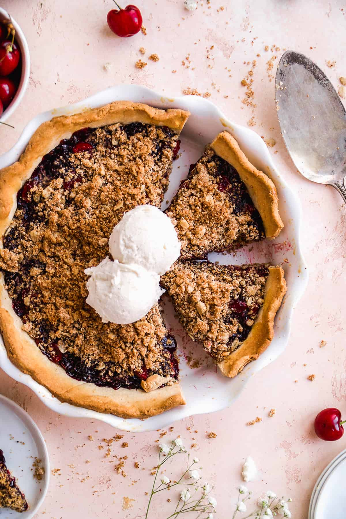Cherry pie cut into slices with ice cream scoops in the middle on a pink surface.