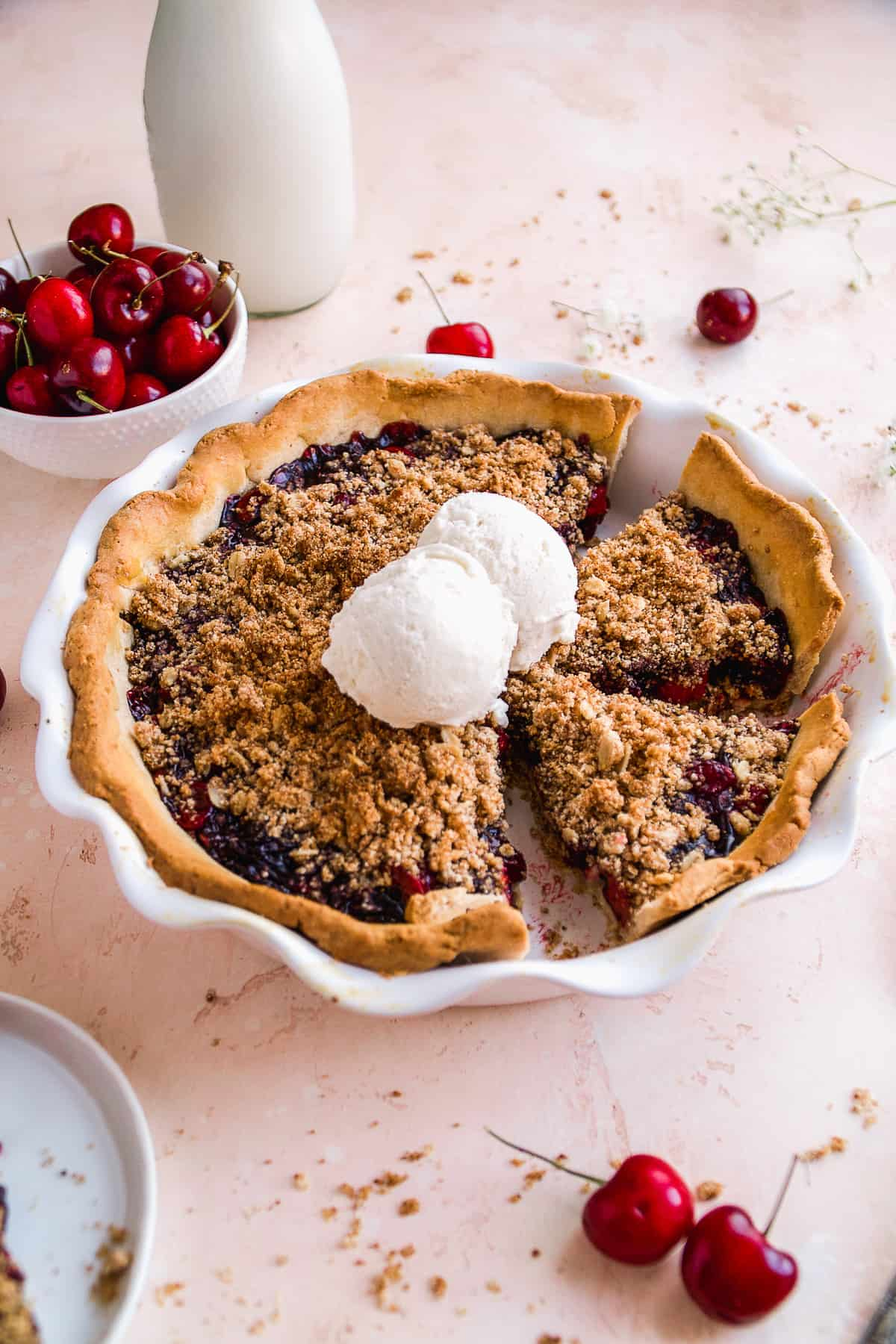 Cherry pie with a gluten free crumble on a pink surface.