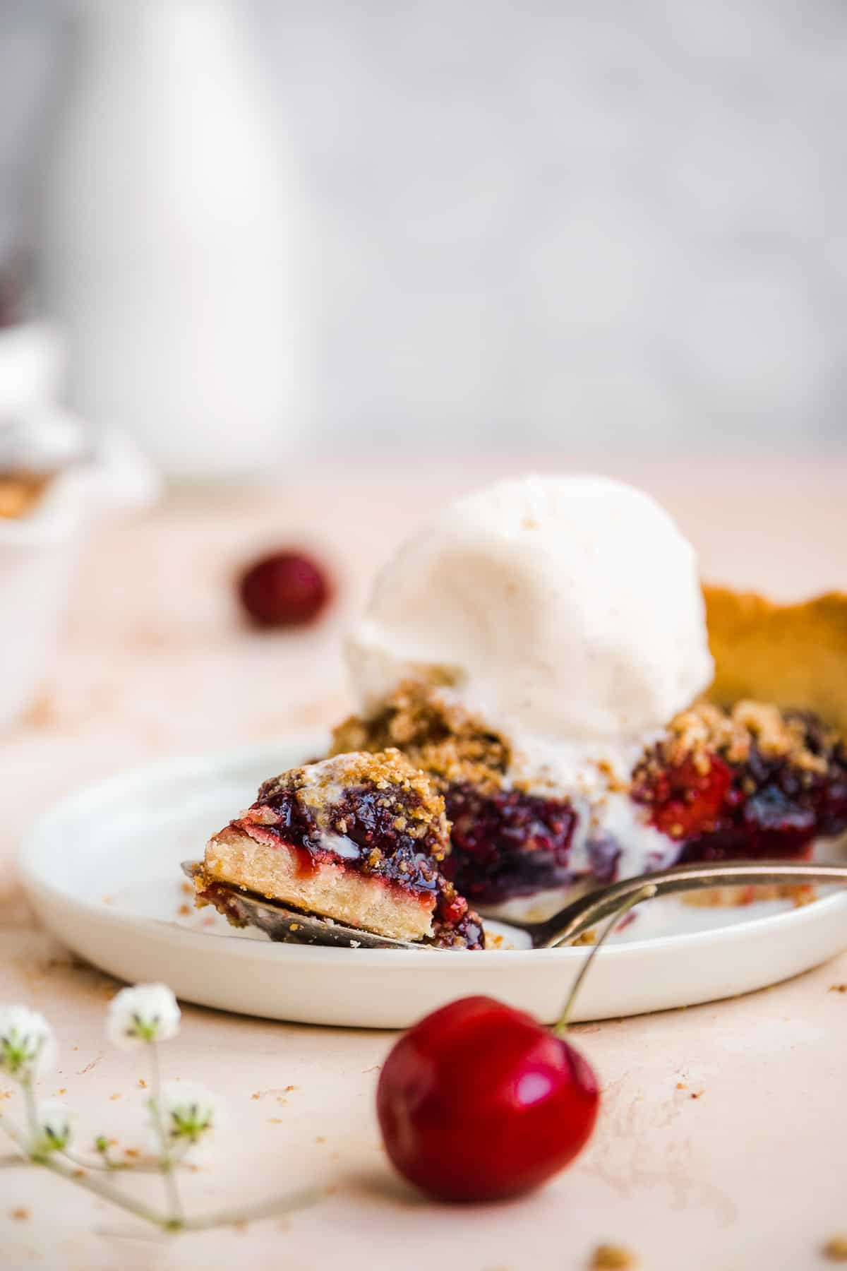 Slice of cherry pie on a white plate with a fork taking a bite.