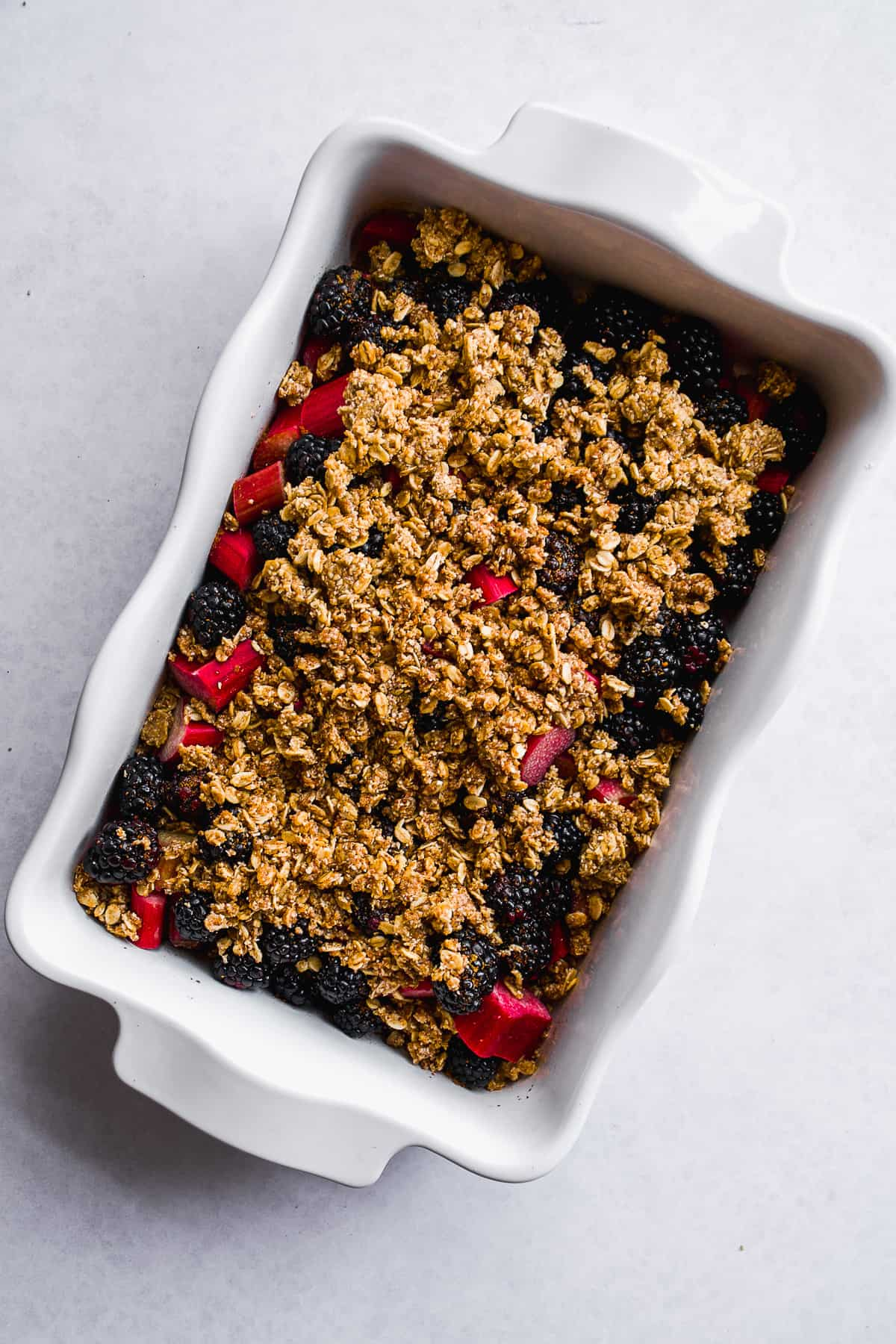 White dish with sliced rhubarb and blackberries and a gluten free crumble on top.