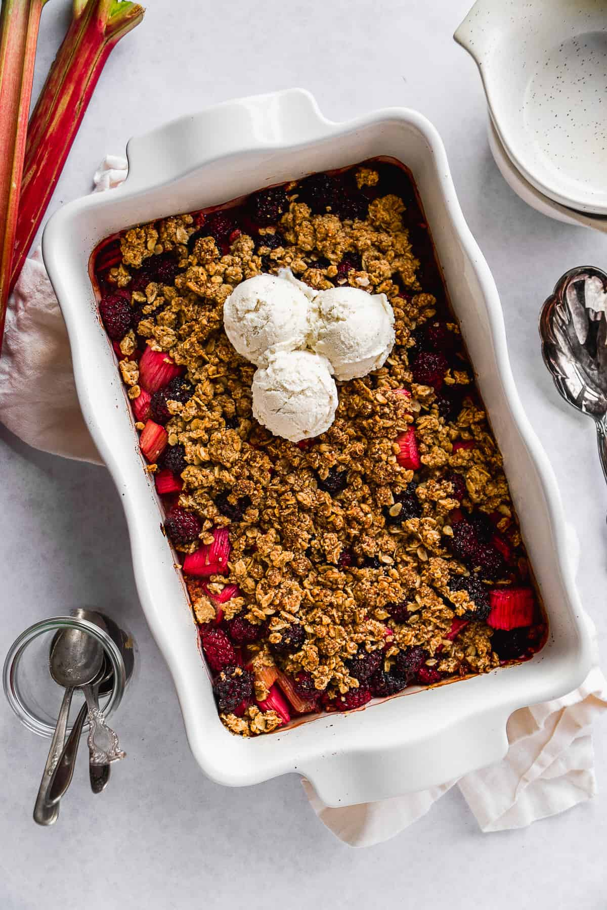 Baked gluten free rhubarb crisp with three scoops of ice cream on top.