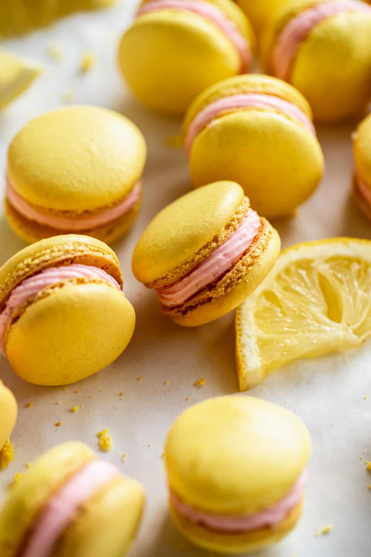 Lemonade macarons with pink icing scattered on surface with a lemon.