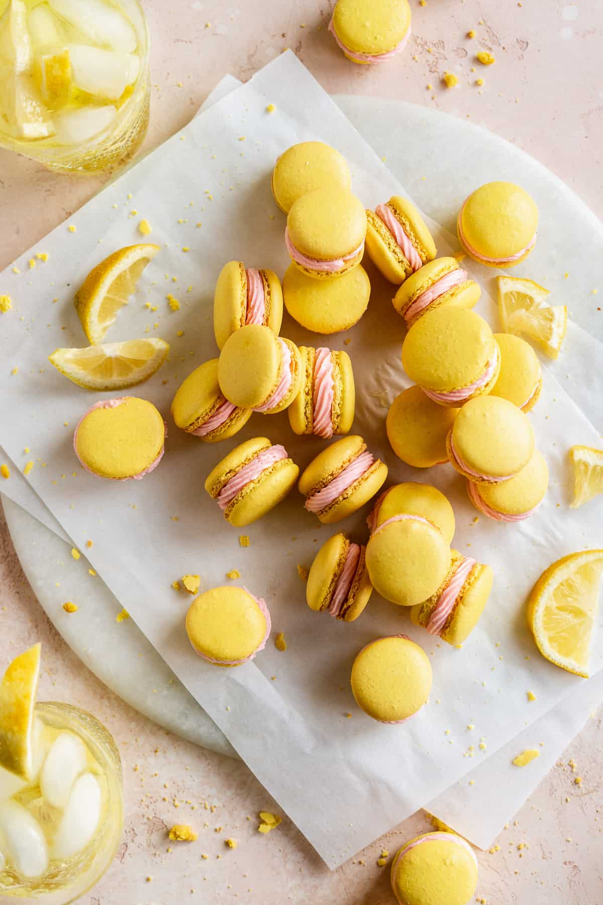 Lemon colored macarons with pink icing piled on round platter.