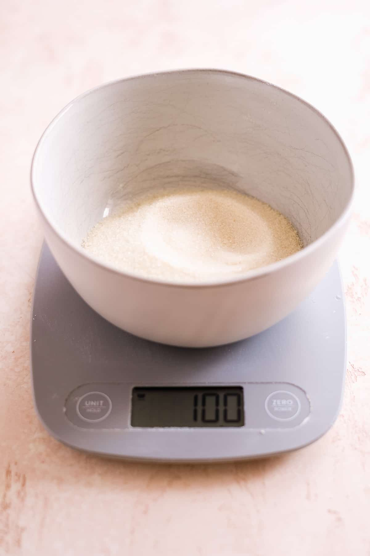 Bowl of sugar on a kitchen scale.