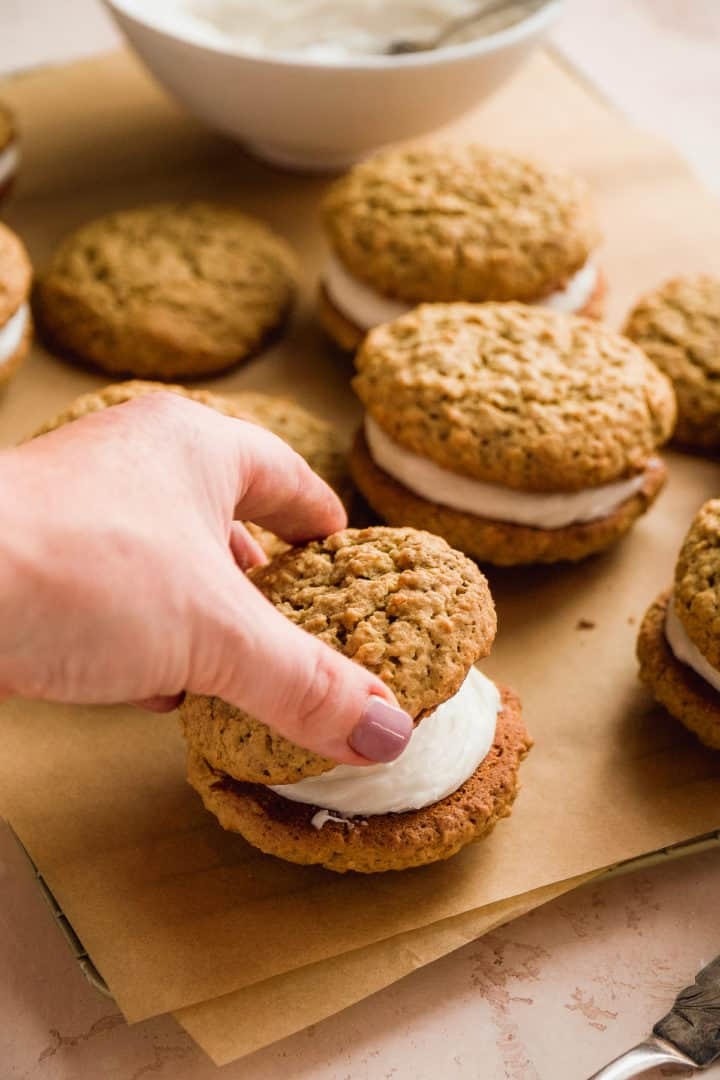 Person sandwiching two gluten free oatmeal cookies with filling in the middle.