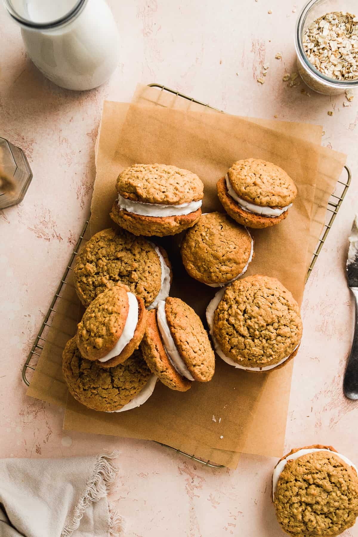 A wire cookie rack with brown parchment paper and gluten free oatmeal cream pies scattered on top.