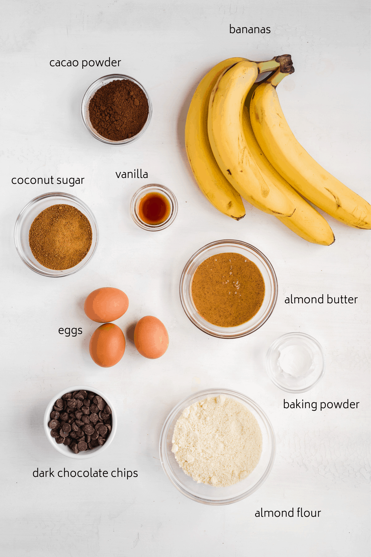Image of healthy double chocolate banana bread ingredients on a white background labeled.