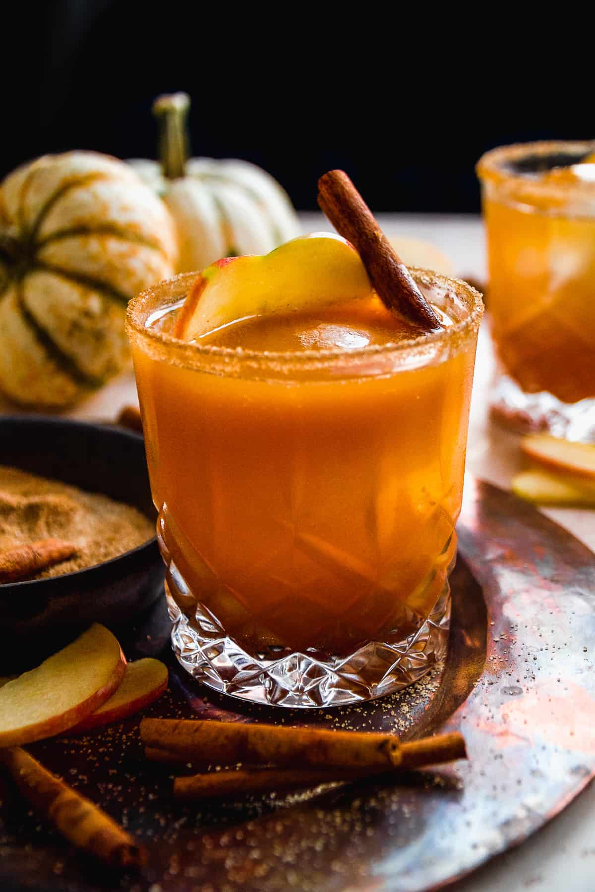 Pumpkin apple cider cocktail on a copper platter with cinnamon stick inside.