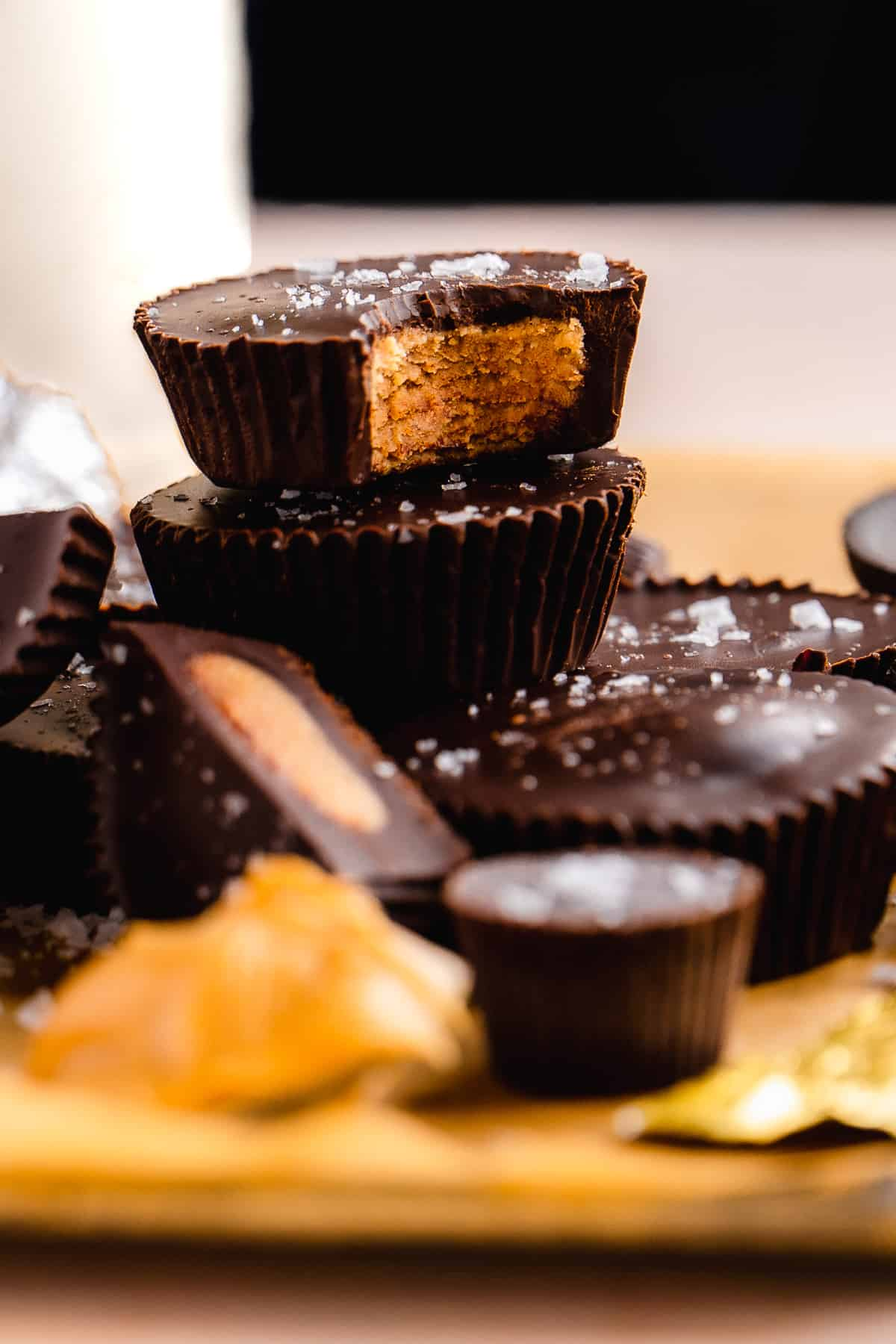 Dark chocolate peanut butter cups stacked on top of one another with sea salt on top.