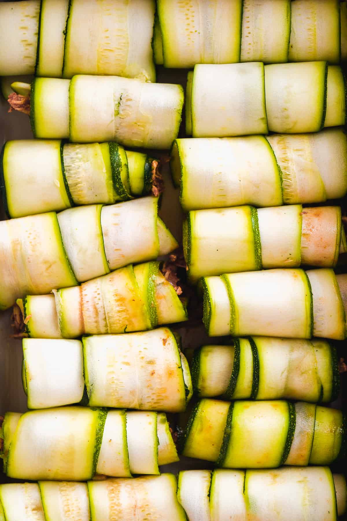 Overhead view of zucchini roll ups with chicken inside lined up in a row.