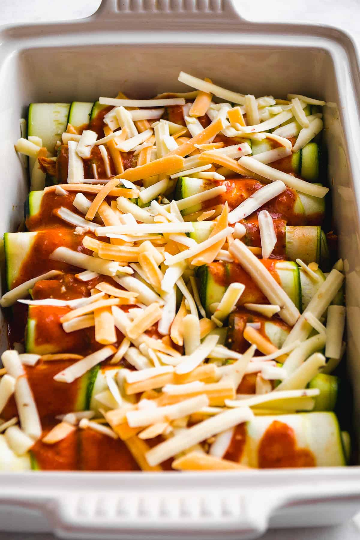 Baking dish with zucchini chicken roll ups topped with enchilada sauce and cheese about to be baked.