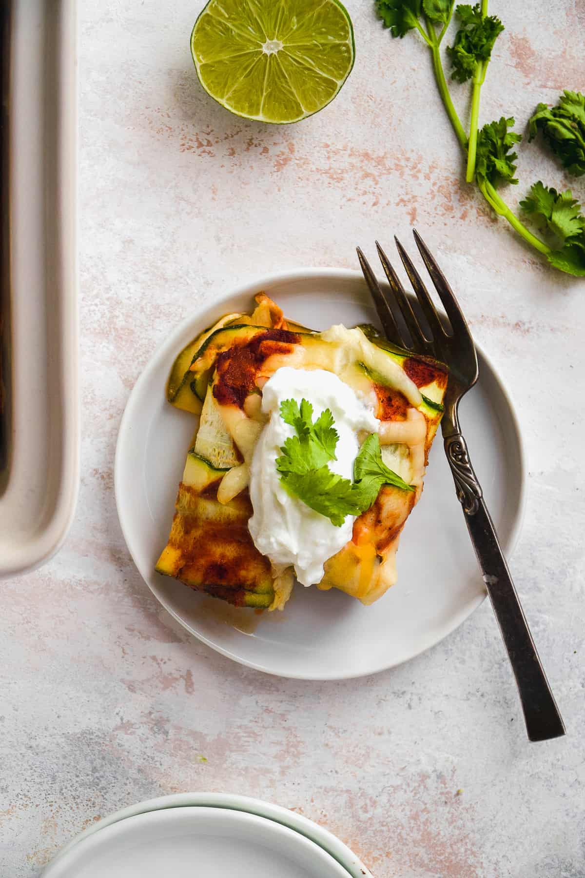 Overhead view of zucchini enchiladas on a white plate with a fork resting on the plate.