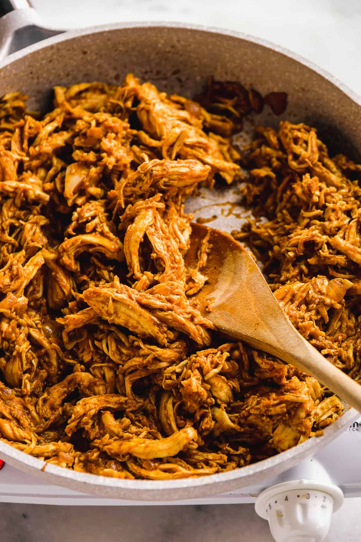 Skillet with pulled spiced chicken and a wooden spoon.