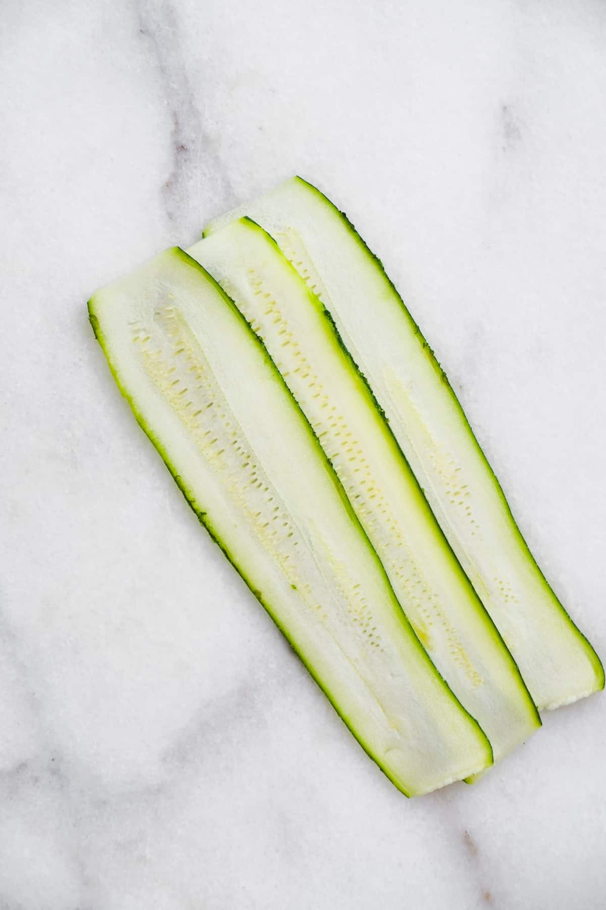 Three zucchini strips overlapping on a marble surface.