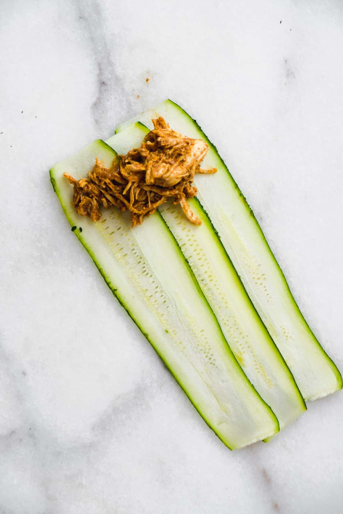 Zucchini strips with pulled chicken about to be rolled up.