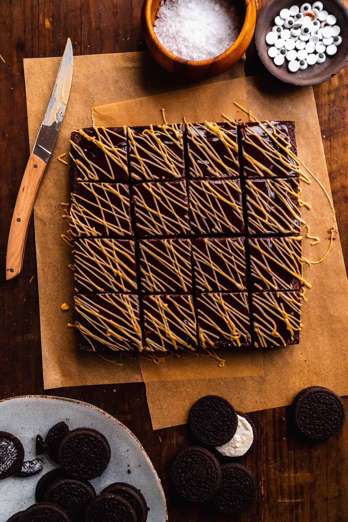 Brownies sliced into squares with almond butter icing drizzled on top on a wooden surface.