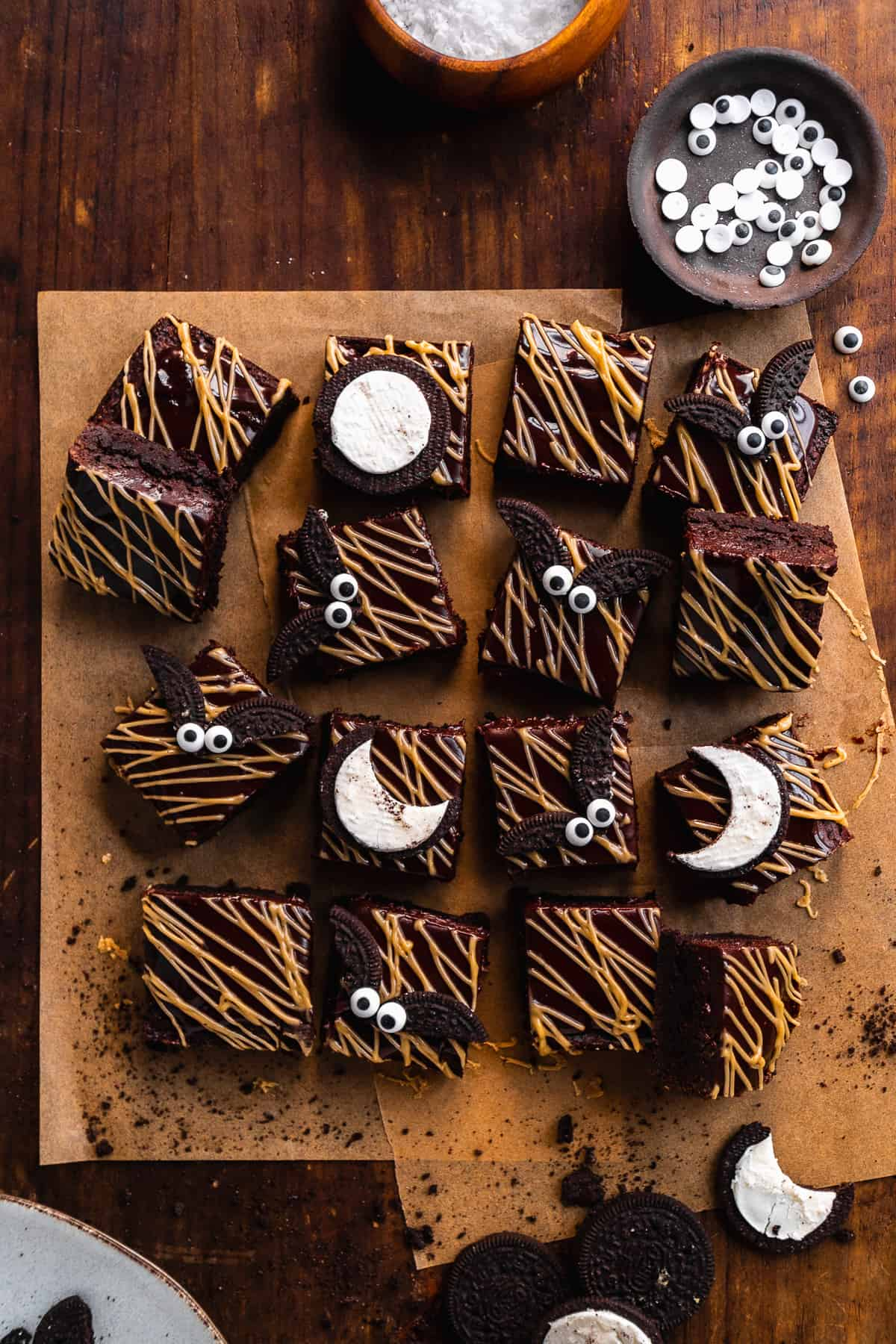 Overhead view of brownies cut into squares with almond butter drizzle and brownies on top made out of Oreos.