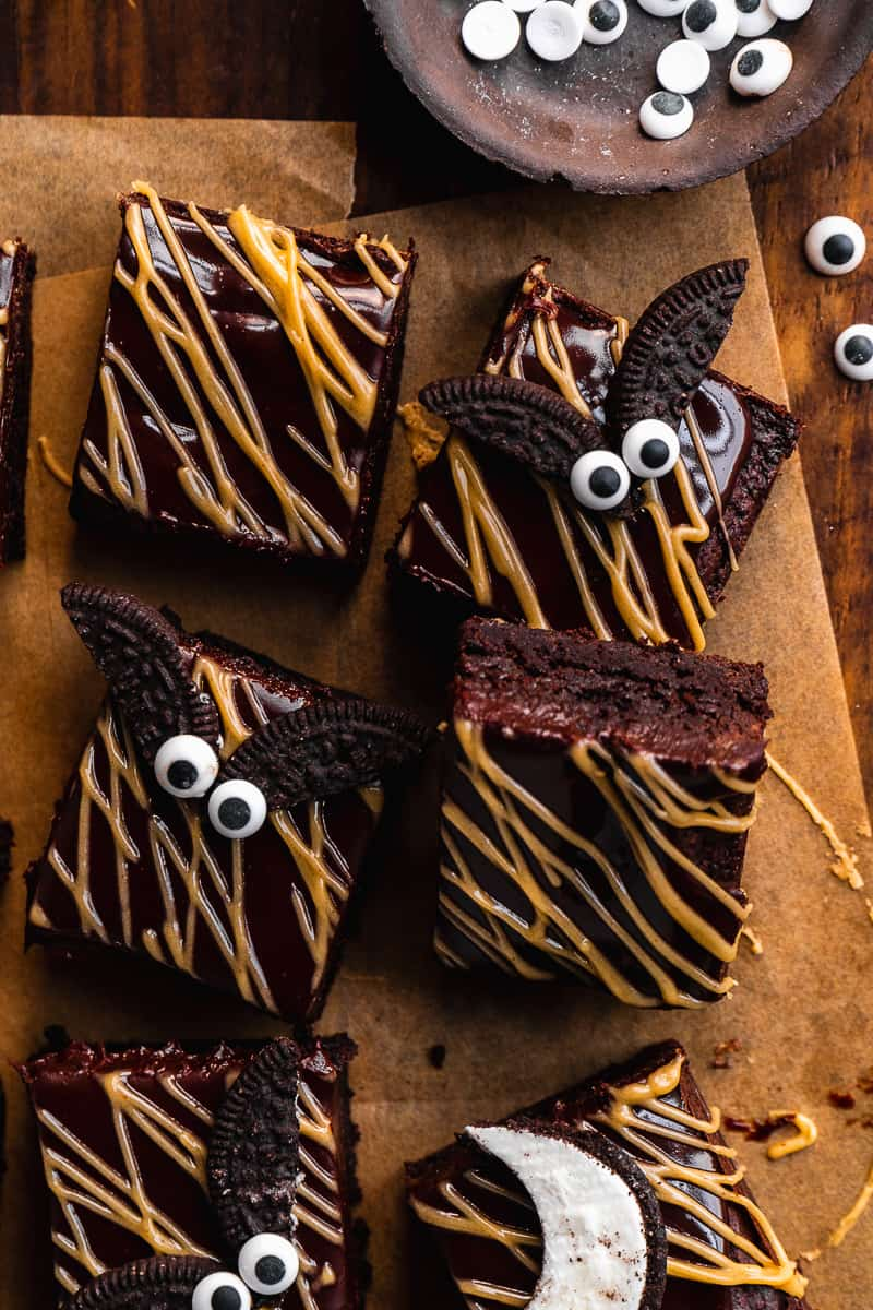 Overhead view of brownies with peanut butter drizzle on top and oreo bats on parchment paper.